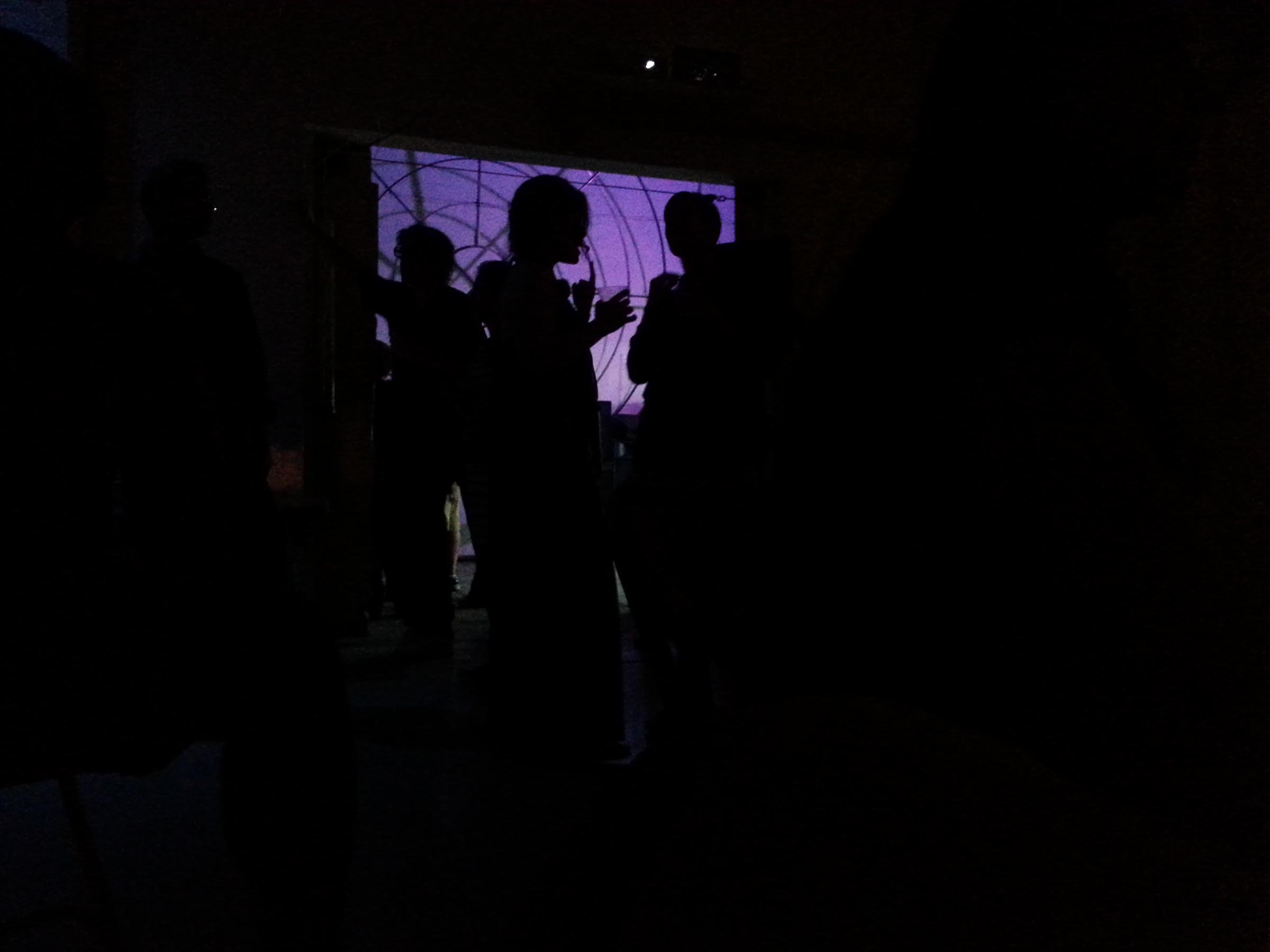 A darkened room with an illuminated panel on the opposite wall glowing purple, with concentric circular designs on it. It's obscured by the silhouettes of guests mingling.