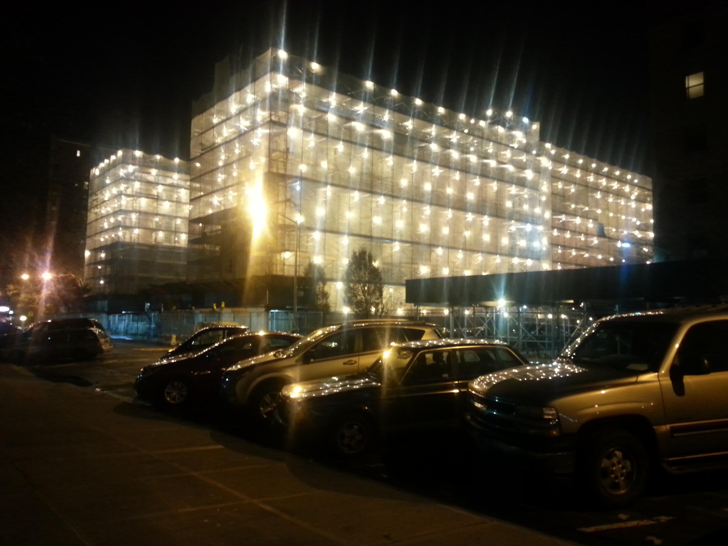 An illuminated building at night. The exterior of the building is covered in netting and hundreds of work lights, making the building appear to be made of light. It's reflected on the hoods of cars parked across the street.