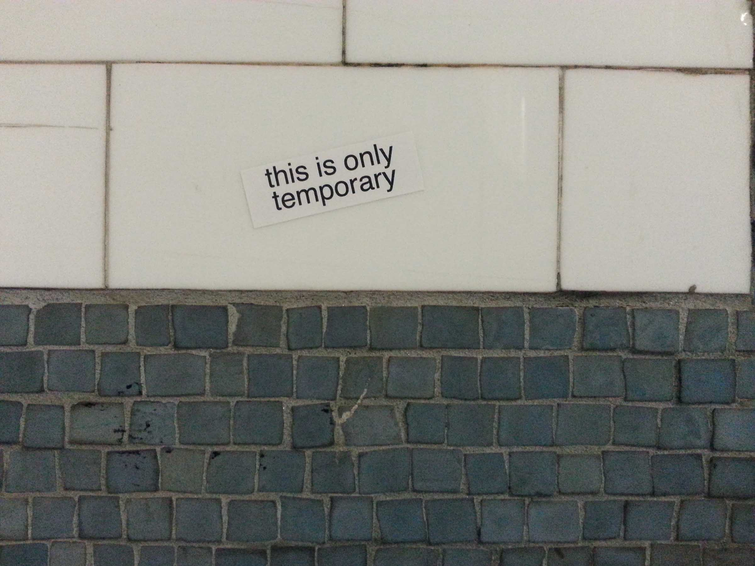 "Photo of the wall of the Astor Place subway station, centered at the height where the wall's facade changes from small, dark, slate-colored tiles to large, smooth, white tiles. A home made sticker reads ""this is only temporary""."