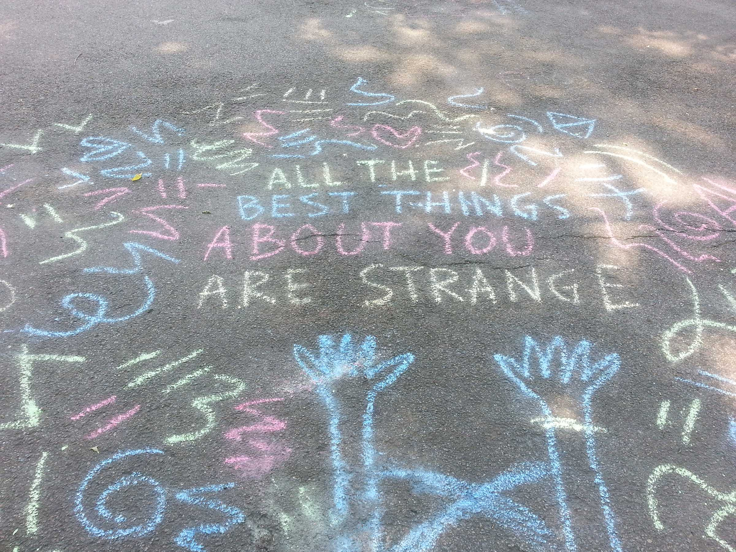 "Chalk art on pavement, in the shade with dappled sunlight. Upstretched arms reach toward the words ""ALL THE BEST THINGS ABOUT YOU ARE STRANGE"", surrounded by squiggly designs in blue, pink, and yellow."