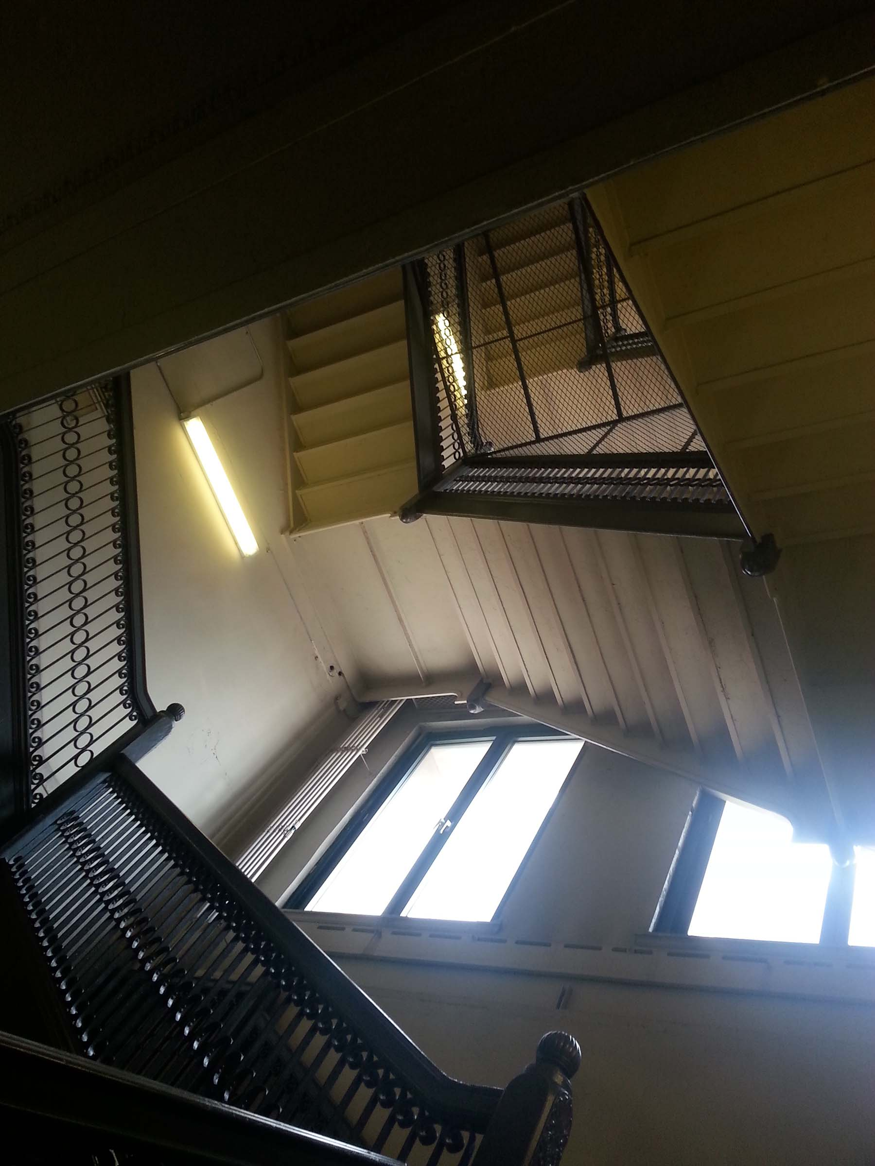 Photo looking upwards through a building stairwell, which spirals down a rectangular shaft, lit by daylight from large windows.