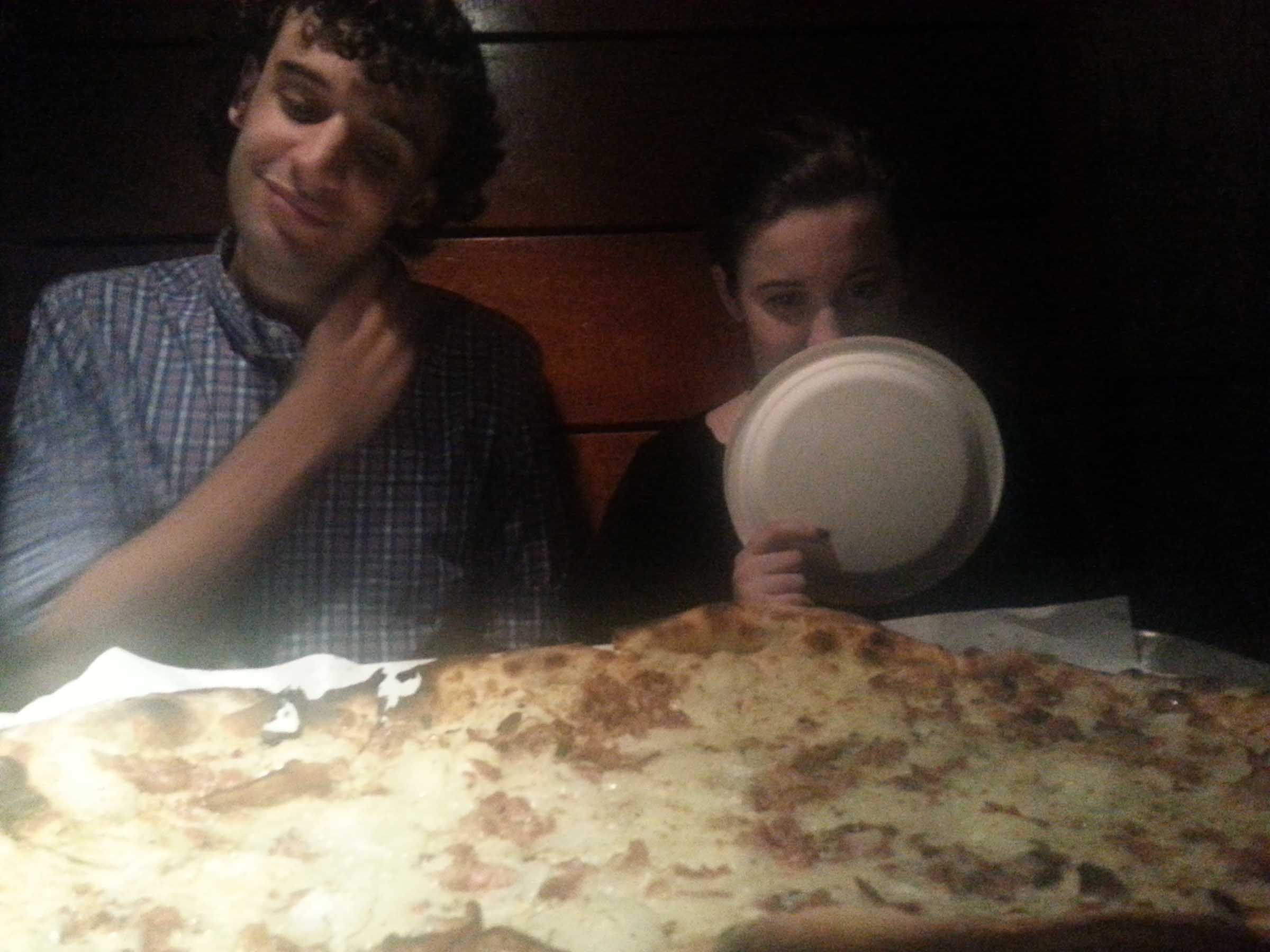 Two people across a restaurant table, pondering a very large rectangular pizza in front of them. One of them holds a paper plate in front of her face.