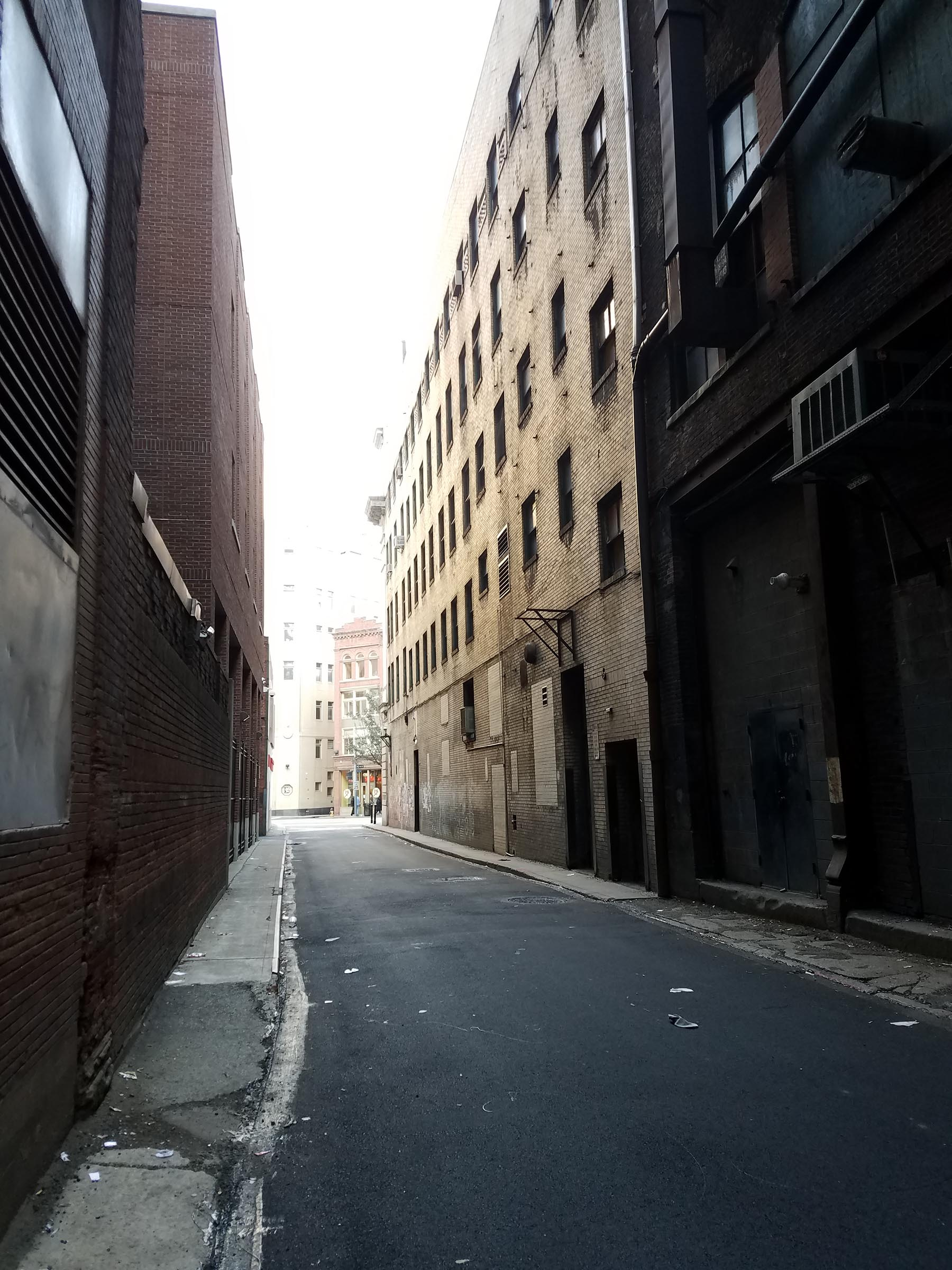 Daytime photo looking down a darkened alley between two five story buildings. The alley ends in about 500 feet where it connects to a brightly lit street.