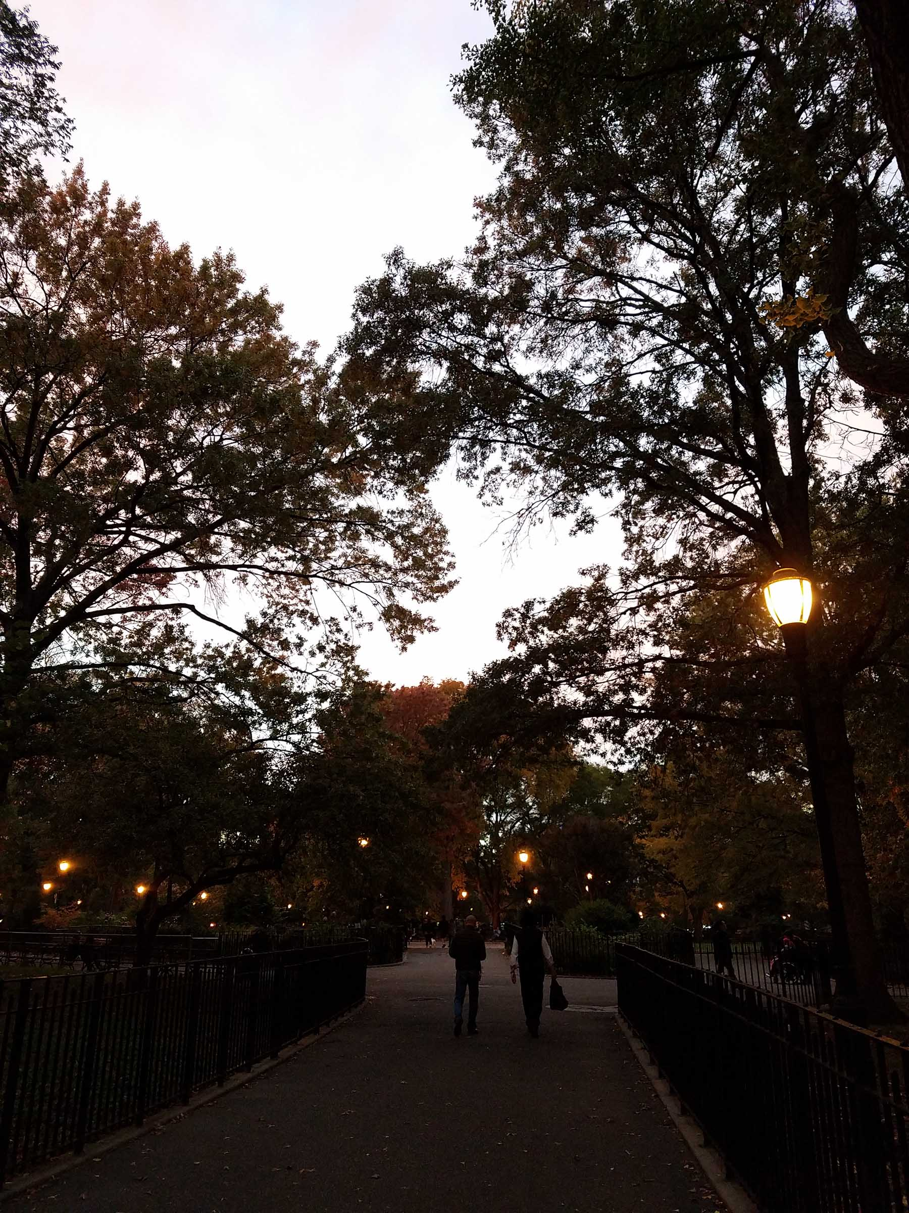 Twilight in a public park walking path. The sky is light but darkening, and orange street lights are on. People, fences, and trees appear mostly as dark silhouettes.