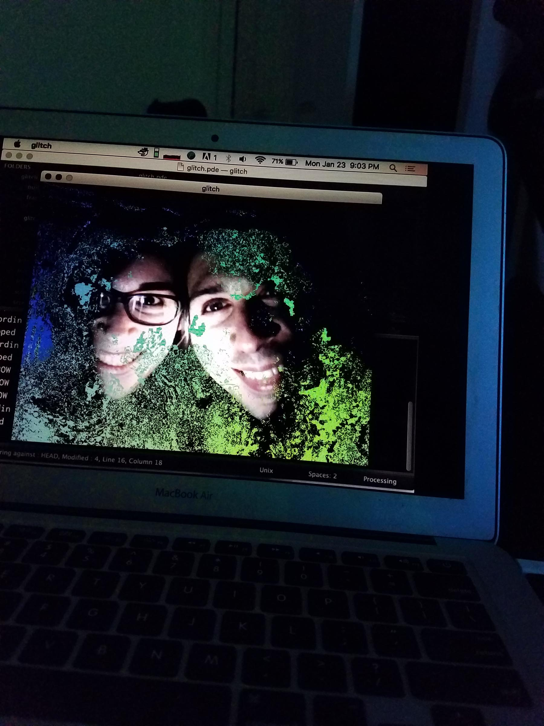 Photo of a laptop screen that displays close-up images of two people. They are smiling, lit from below by a light in an otherwise dark room, and the picture is slightly garbled by green visual noise.