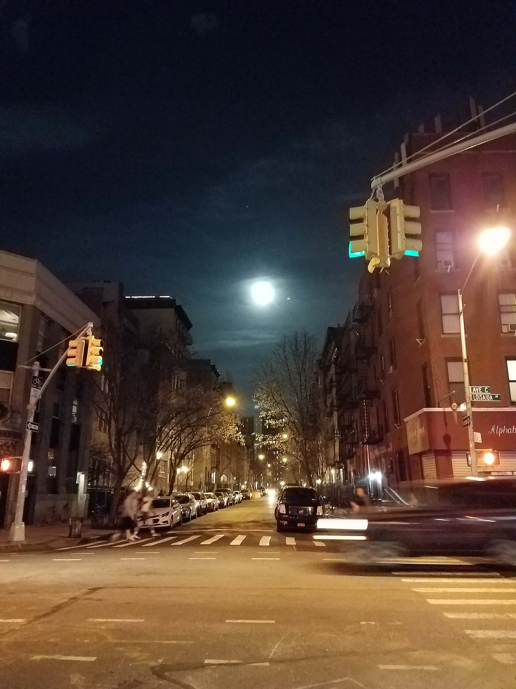 Photo of the moon at night, taken at a street intersection, and looking straight down a road. A car or truck is blurred by its own movement as it crosses the foreground.