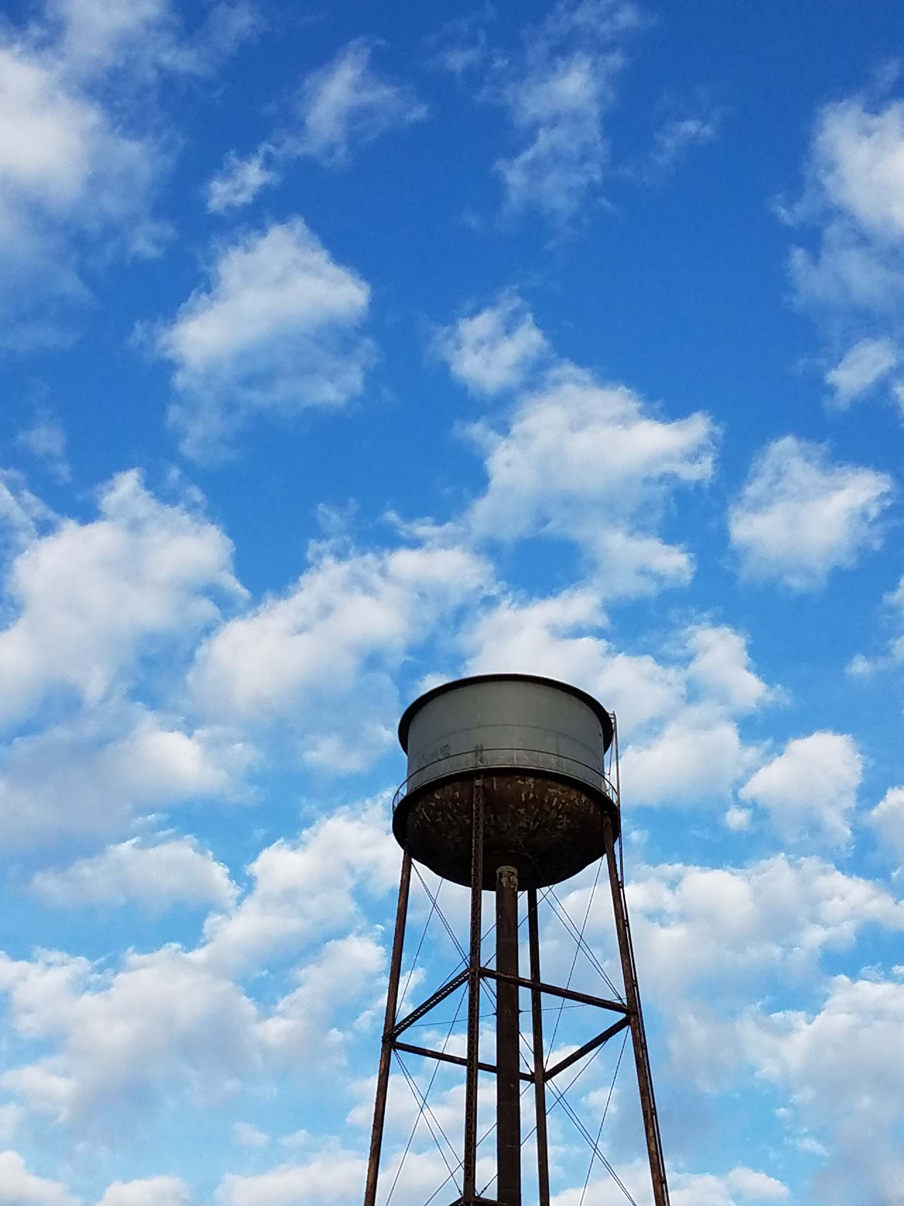 A water tower against a blue sky, filled with white clouds.