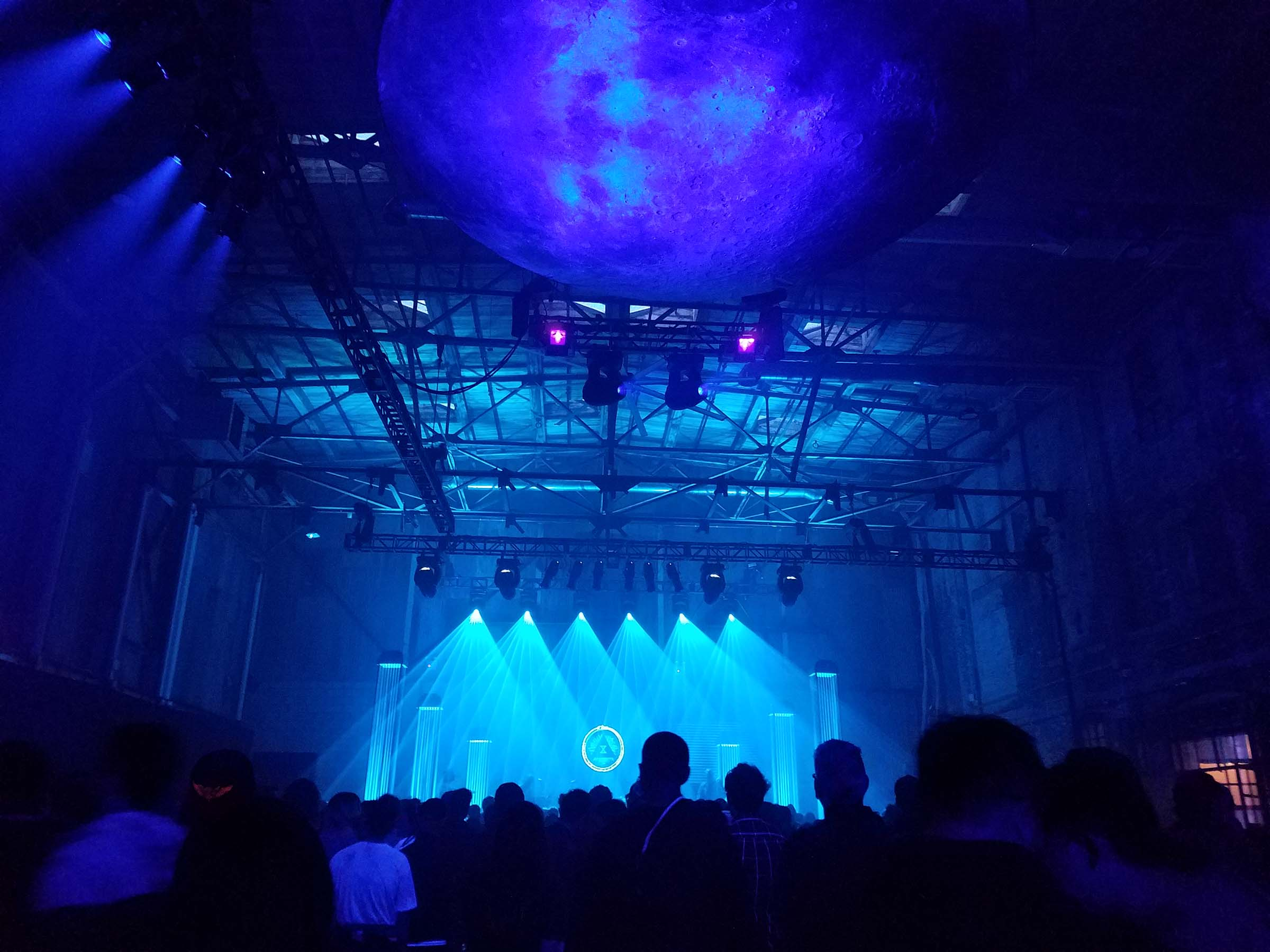 A performance hall, lit with dim blue lights. The stage is illuminated with brighter blue lights focused in triangular beams. The heads of the audience are visible in silhouette against the stage lighting. A disc decorated like the moon hangs from the ceiling.