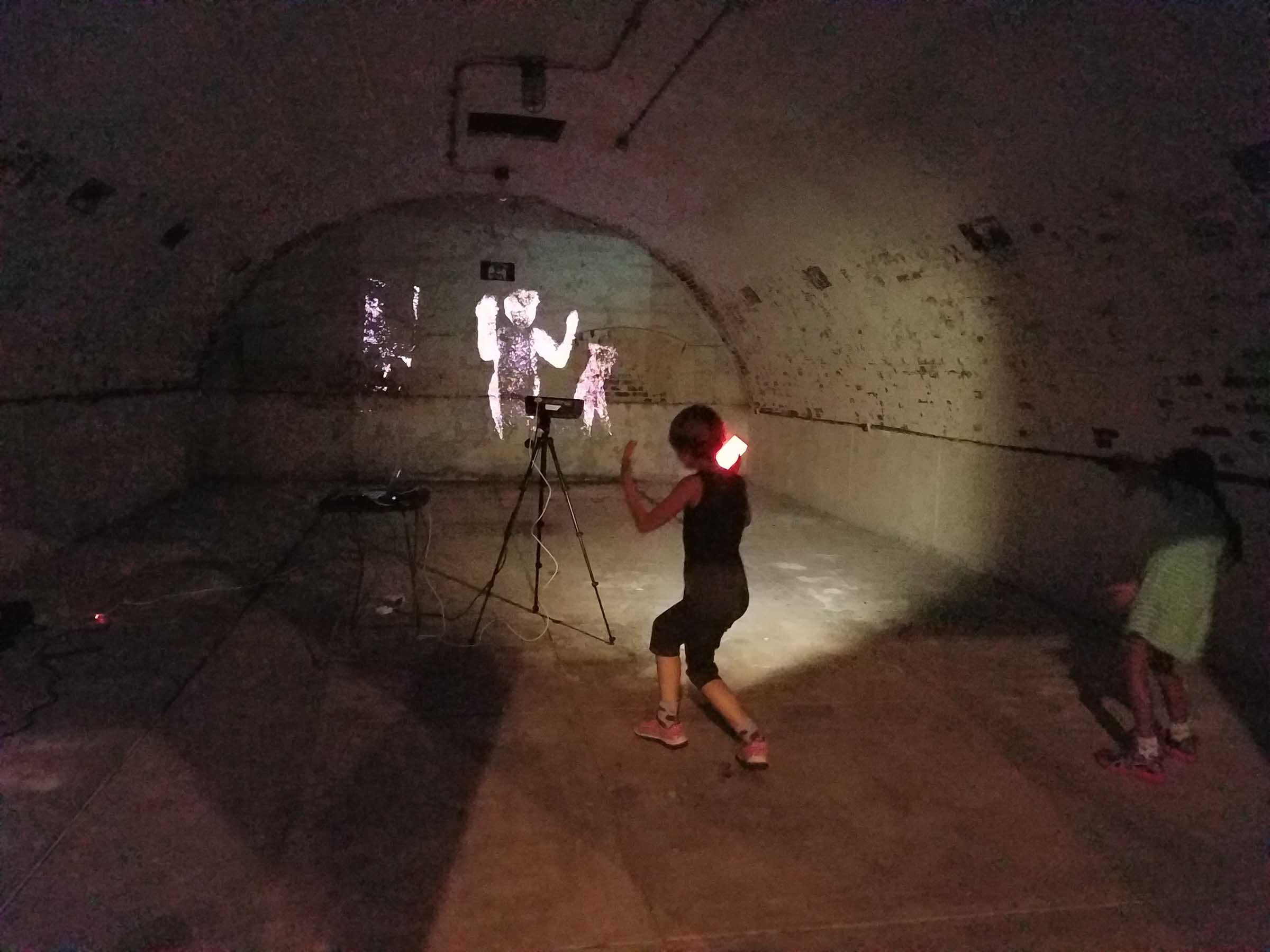 A darkened concrete chamber with a projector casting bright outlines of the people who step inside. A young child dances in front of it, using their phone as a flashlight to see where they are, while a friend watches from the side.