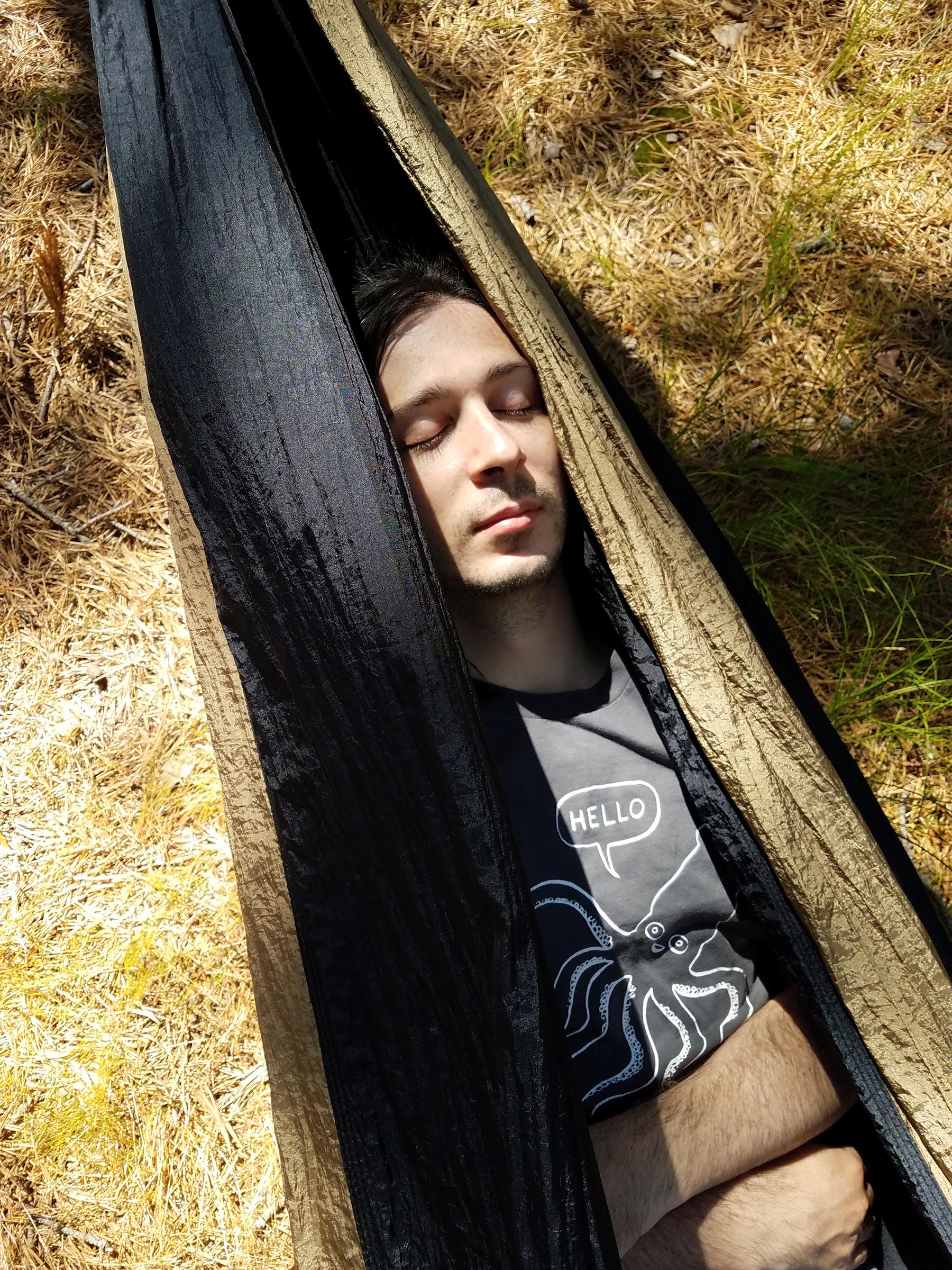 A person with their eyes closed, taking an afternoon nap in a hammock.