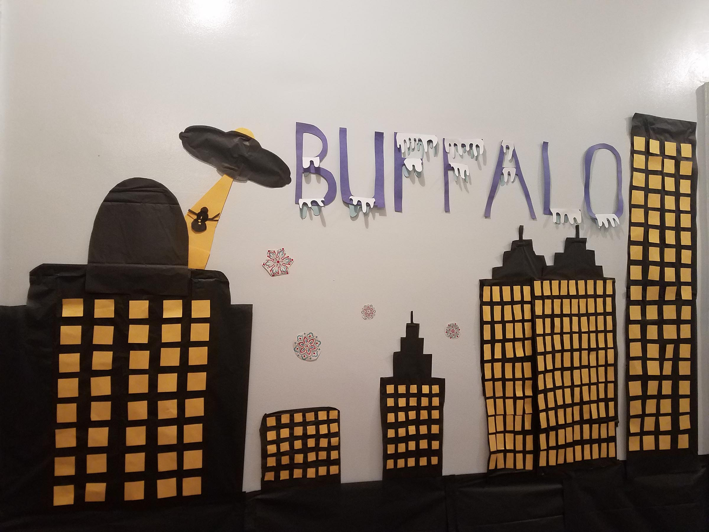 "Construction paper decorations on a wall. Purple text reads ""BUFFALO"", with white icicles hanging from the letters. Below it is a skyline of black bulidings with yellow windows. There is also an alien UFO lifting a snowman out of a building with a yellow beam of light."