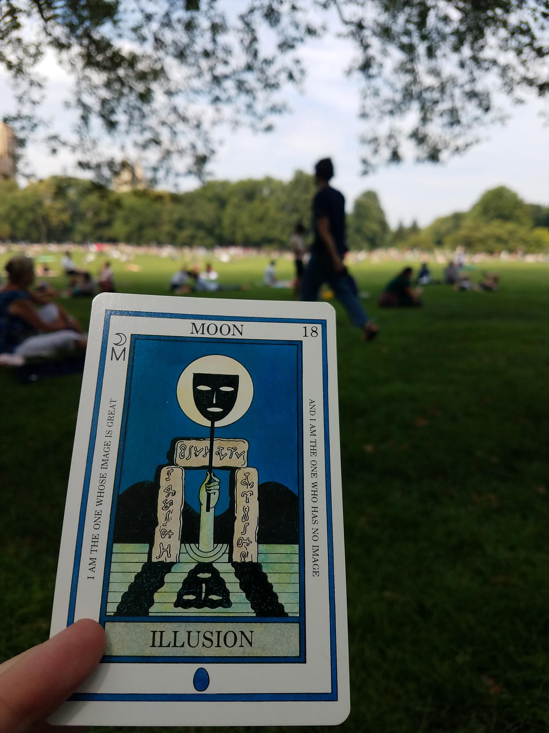 "In the foreground, a ""MOON"" tarot card whose illustration is an upstretched arm, beneath some standing stones with inscriptions, holding a mask on a stick up against the moon, which is high in the sky. In the background are people gathered on a grassy lawn."