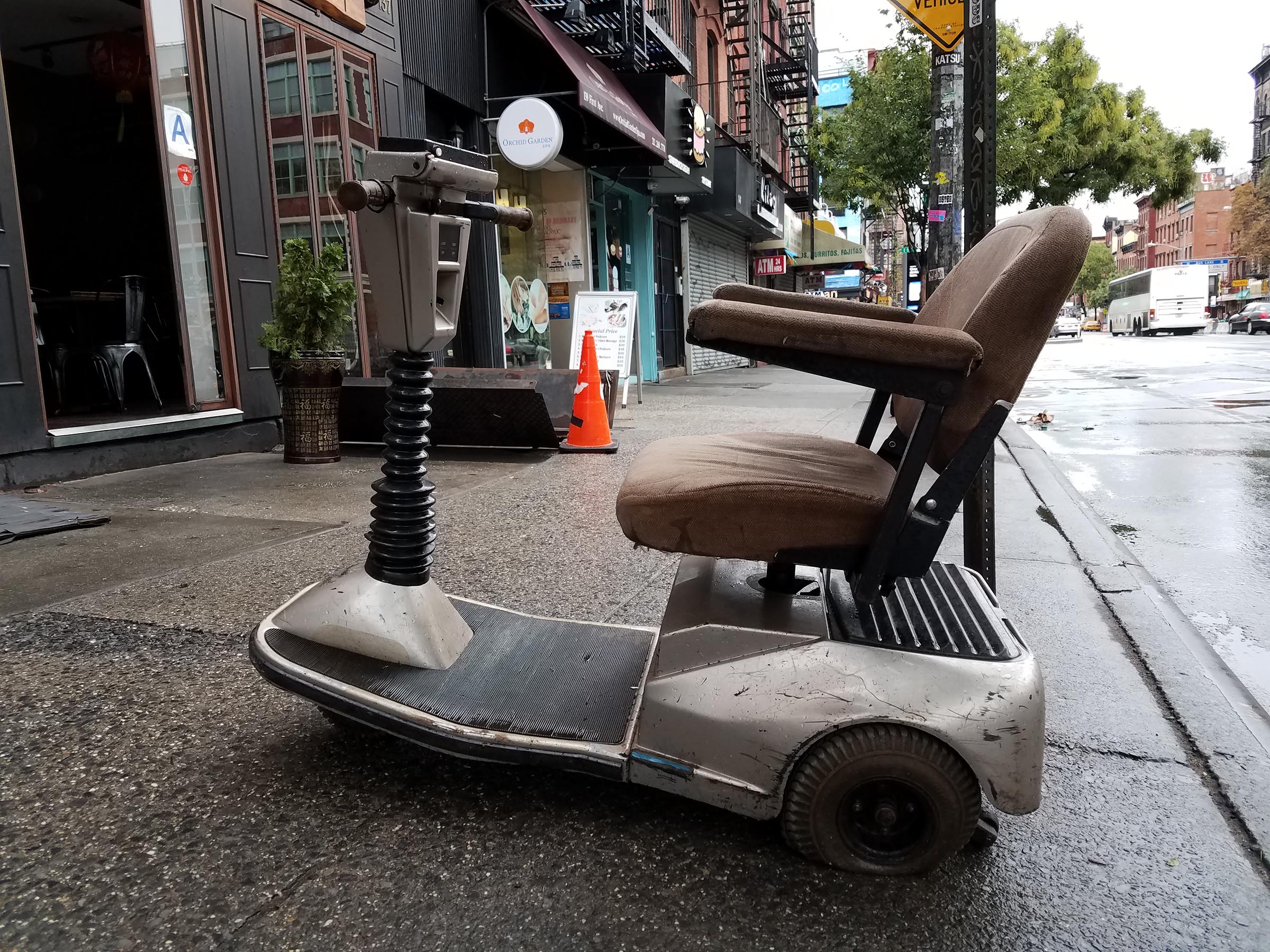 A beige, beat-up sit-down scooter with a flat tire, parked at an odd angle on the sidewalk. The concrete is slick with recent rain.
