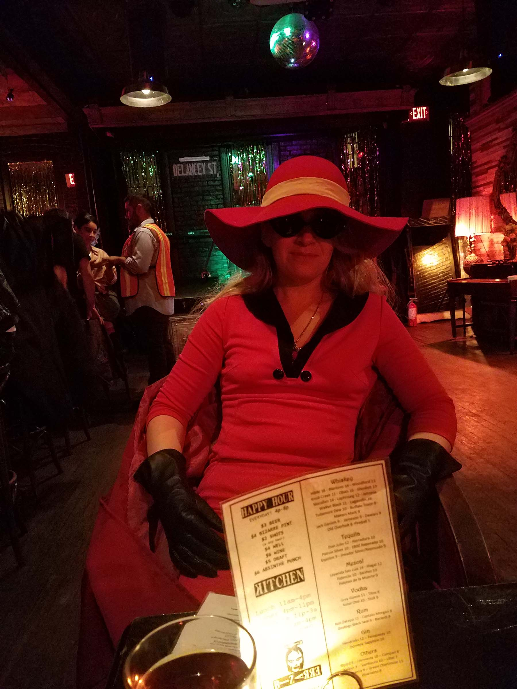 Sitting across the table in a dimly lit bar from a person wearing a red hat and red dress, gloves, and dark sunglasses.