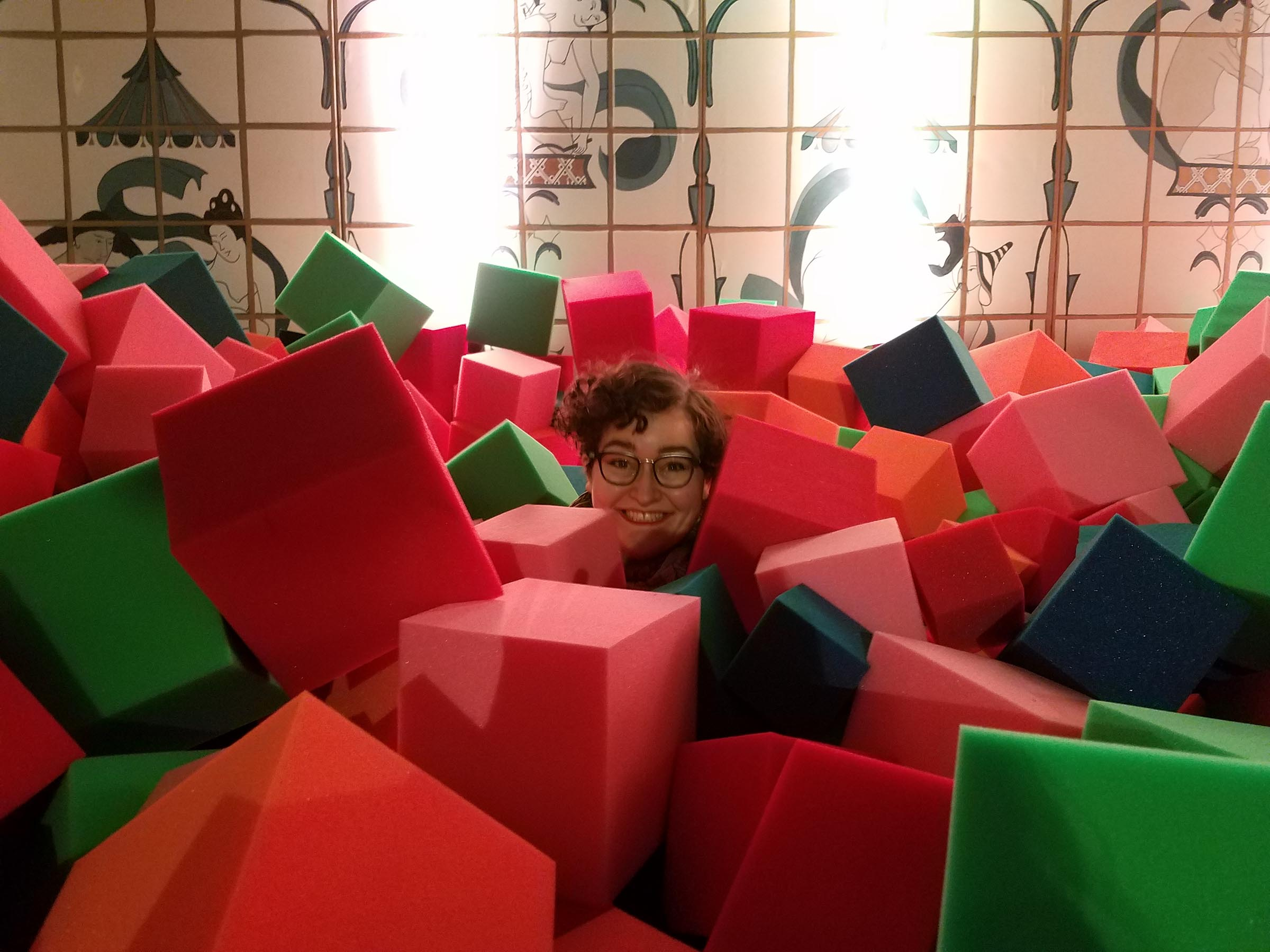 A deep pile of red and green foam cubes covering the floor, like a ball pit. A person hiding beneath the foam cubes peeks their head out and smiles at the camera. The opposite wall is covered in faux Japanese erotic art, for some reason.