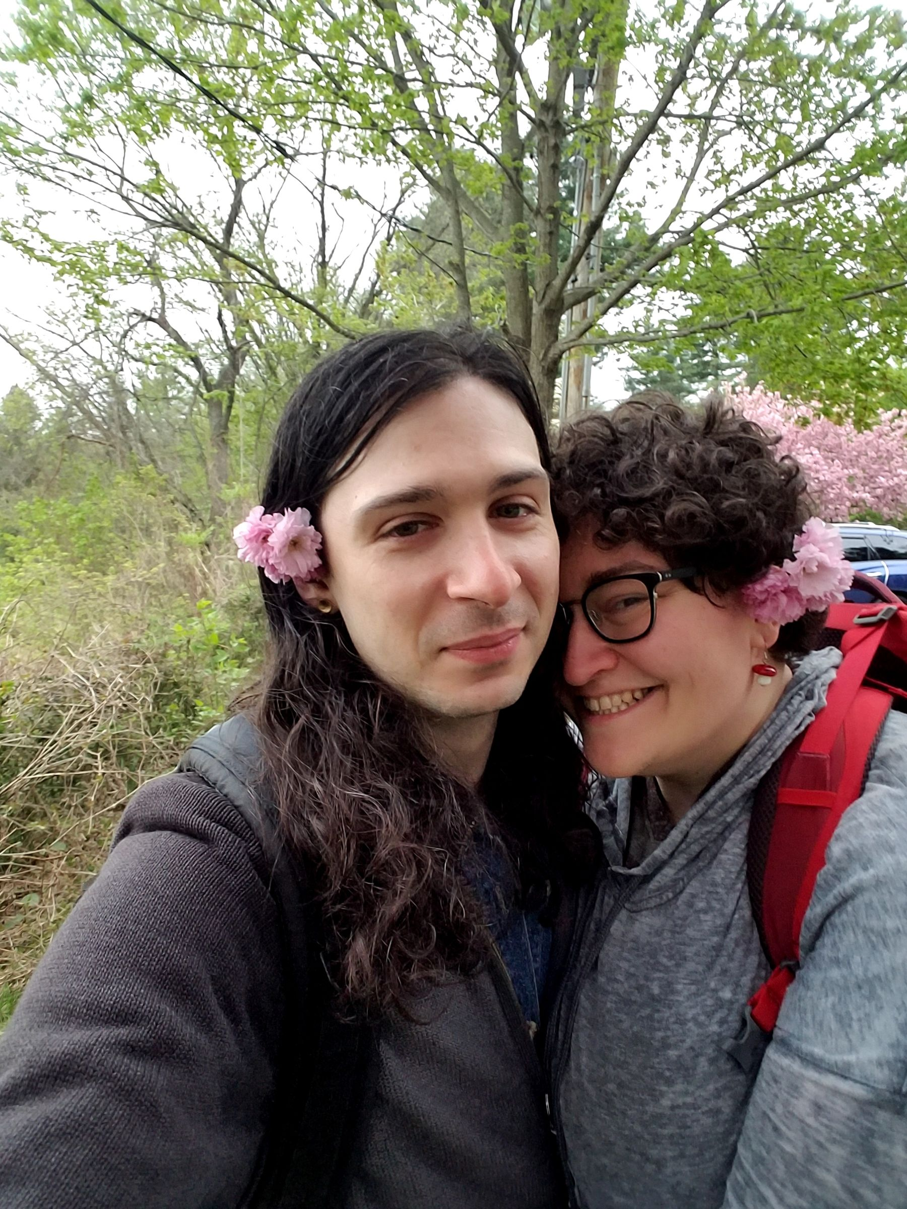 A selfie of two people in front of a tree. They are smiling into the camera, and each have pink flowers in their hair.