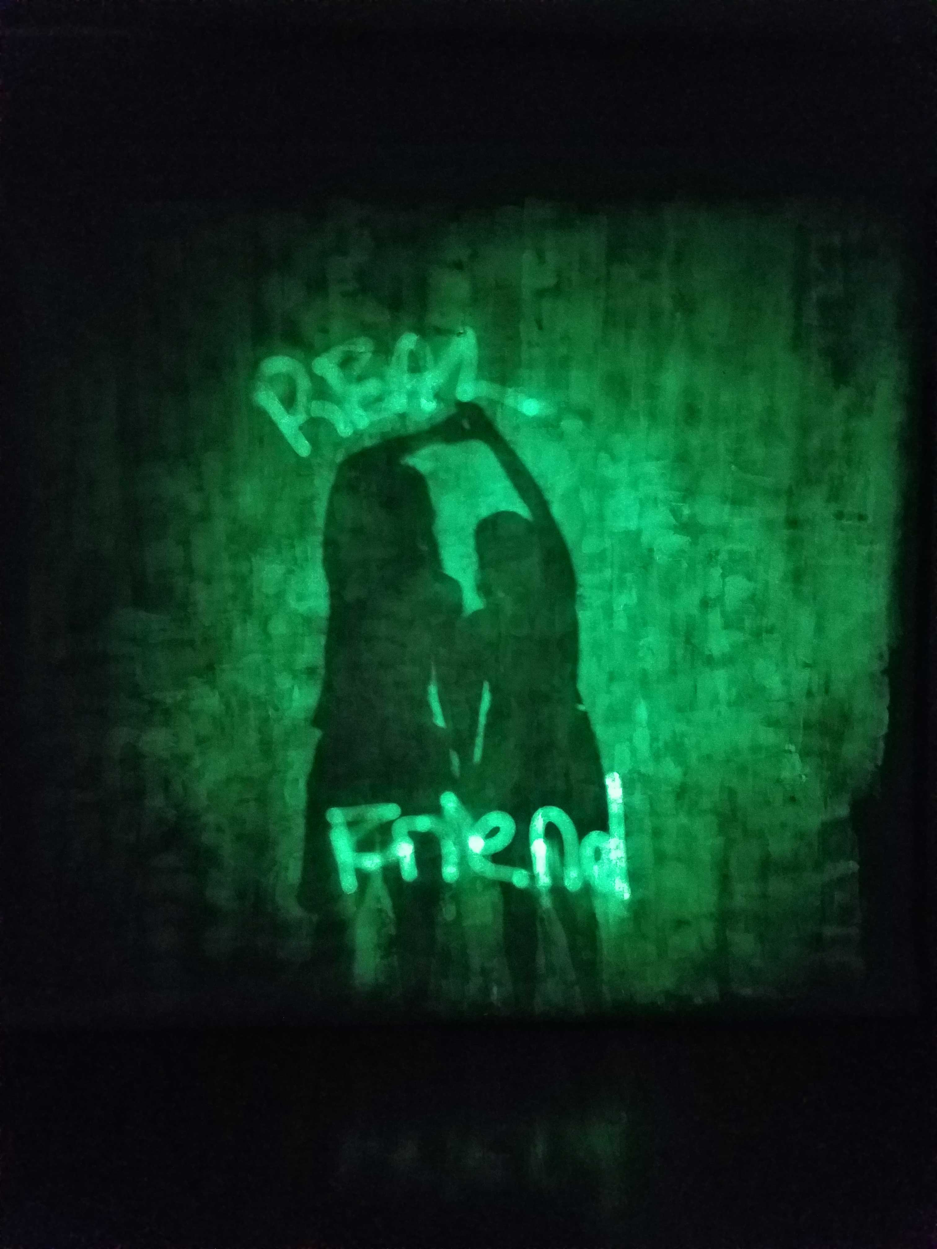 "A photosensitive sheet glowing green in the darkness. The profiles of two people holding hands appear as darker silhouettes. The words ""REAL FRIEND"" are written above and below the figures in bright glowing letters."