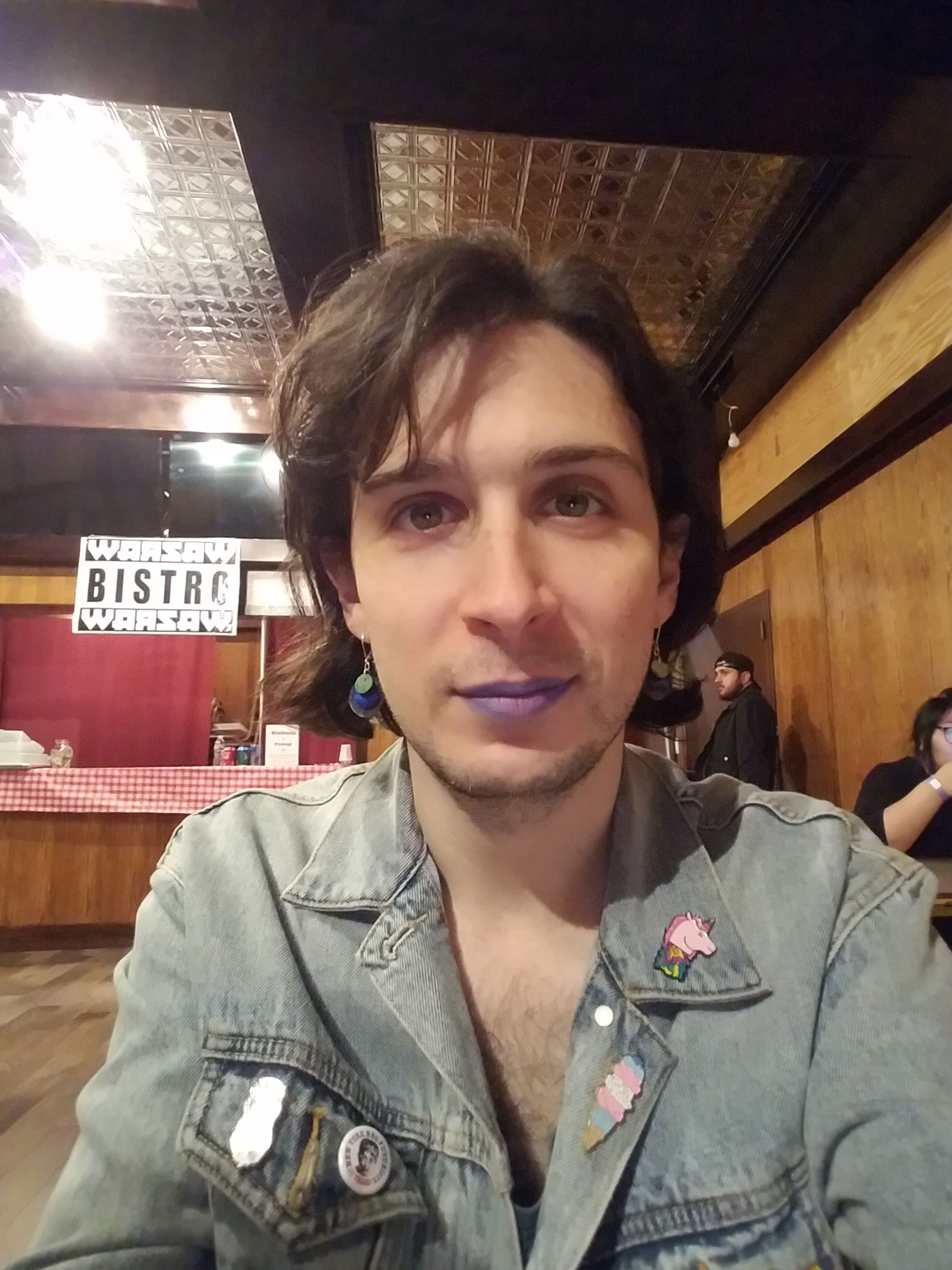 "An indoor selfie of a person in a denim jacket with enamel pins on its lapels. Behind them are tables with people eating and a food counter. A sign reads ""WARSAW BISTRO""."