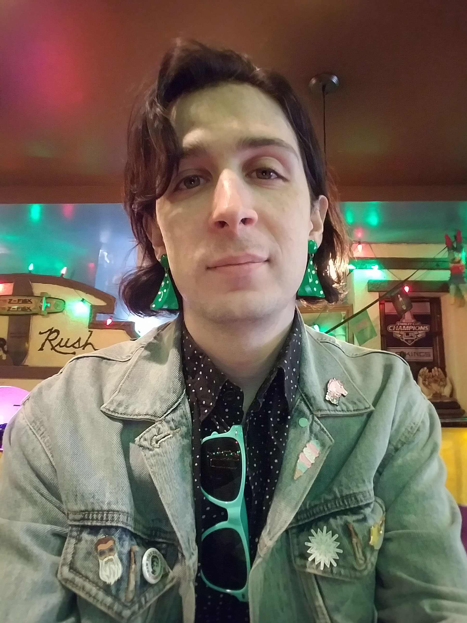 An indoor selfie of a person in a colorfuly lit restaurant. They are wearing a black and white dotted shirt and large green earrings.