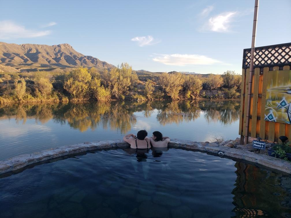 An outdoor pool overlooking a river in late afternoon. Scrubby hills and a mountain range are in the distance on the horizon. Two people are in the pool, leaning against the edge and looking at each other.