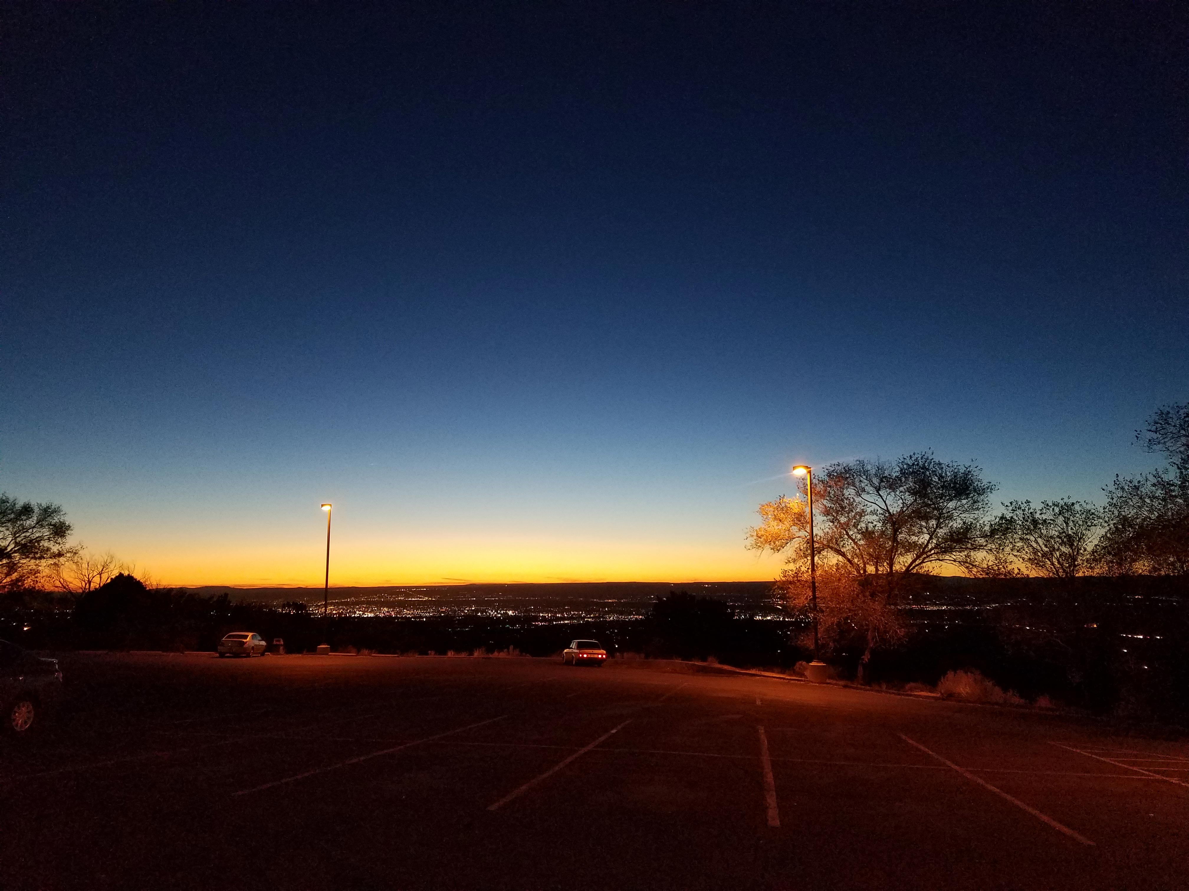 A nearly empty parking lot, overlooking the lights of a city in the distance. The sun has just set, so the sky fades from dark blue to yellow on the horizon. Two cars sit apart from each other near the edge of the lot.