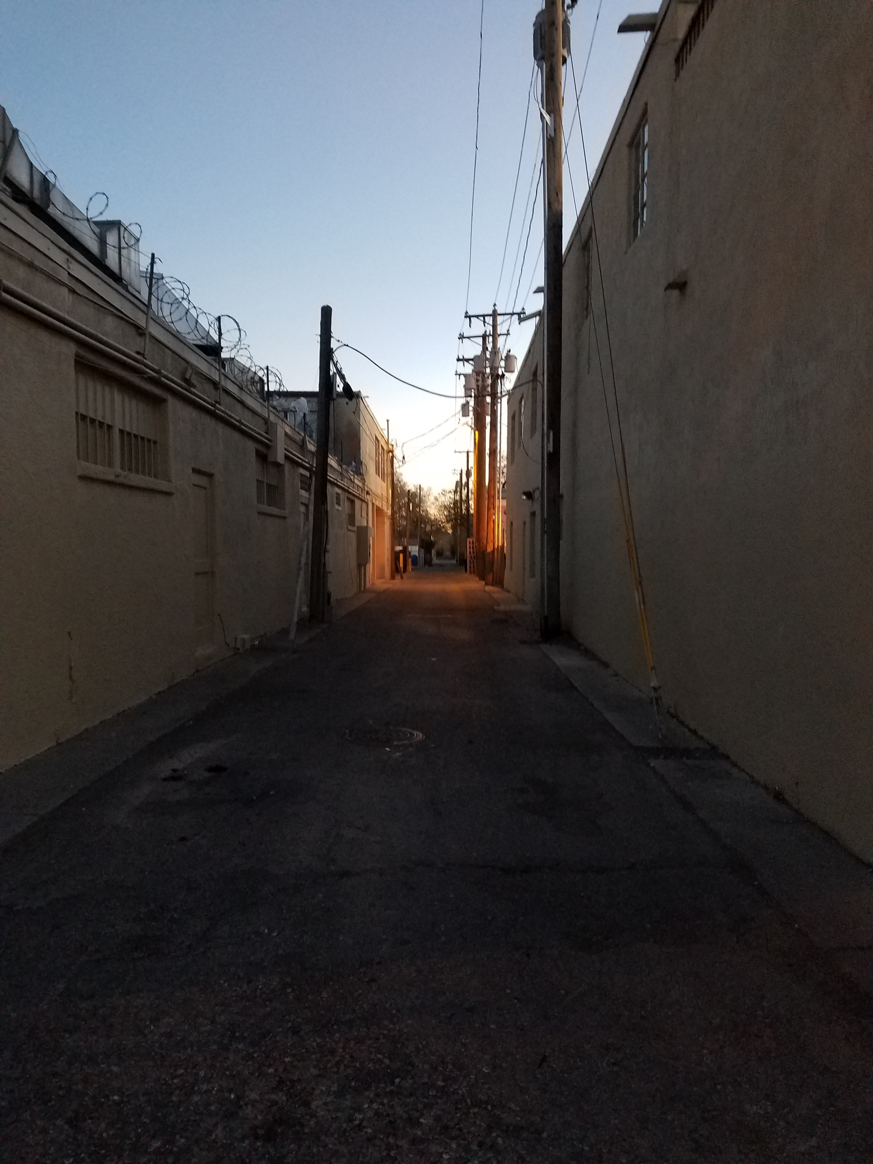 An alley between two beige buildings at dusk. The building to the left has blocked off windows and barbed wire coiled along the top. 1940s style telephone poles line both sides of the alley.