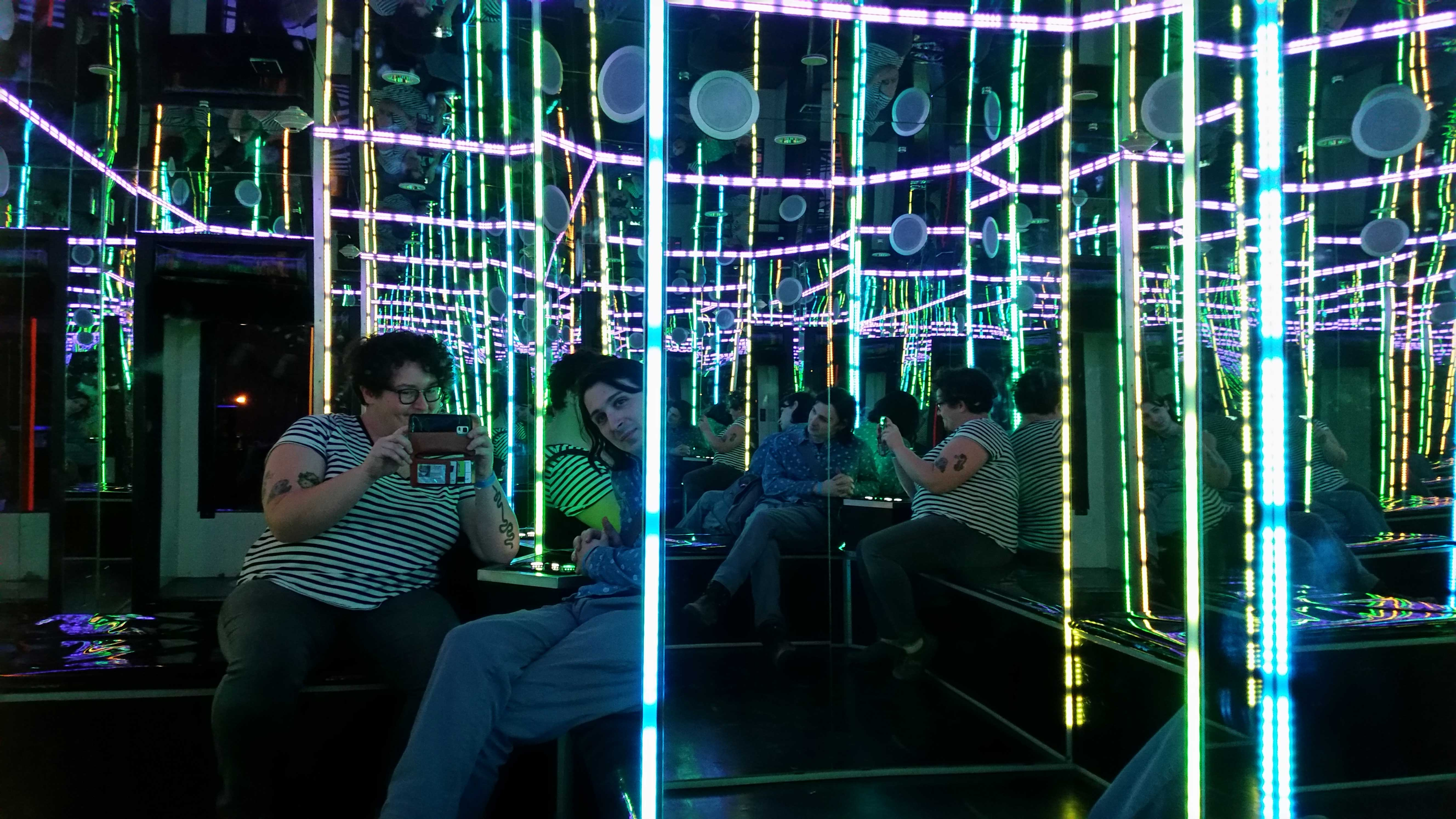 Picture of a mirrored room lit by blue-green fluorescent lights. The photographer and another person are visible in several reflections on the walls.
