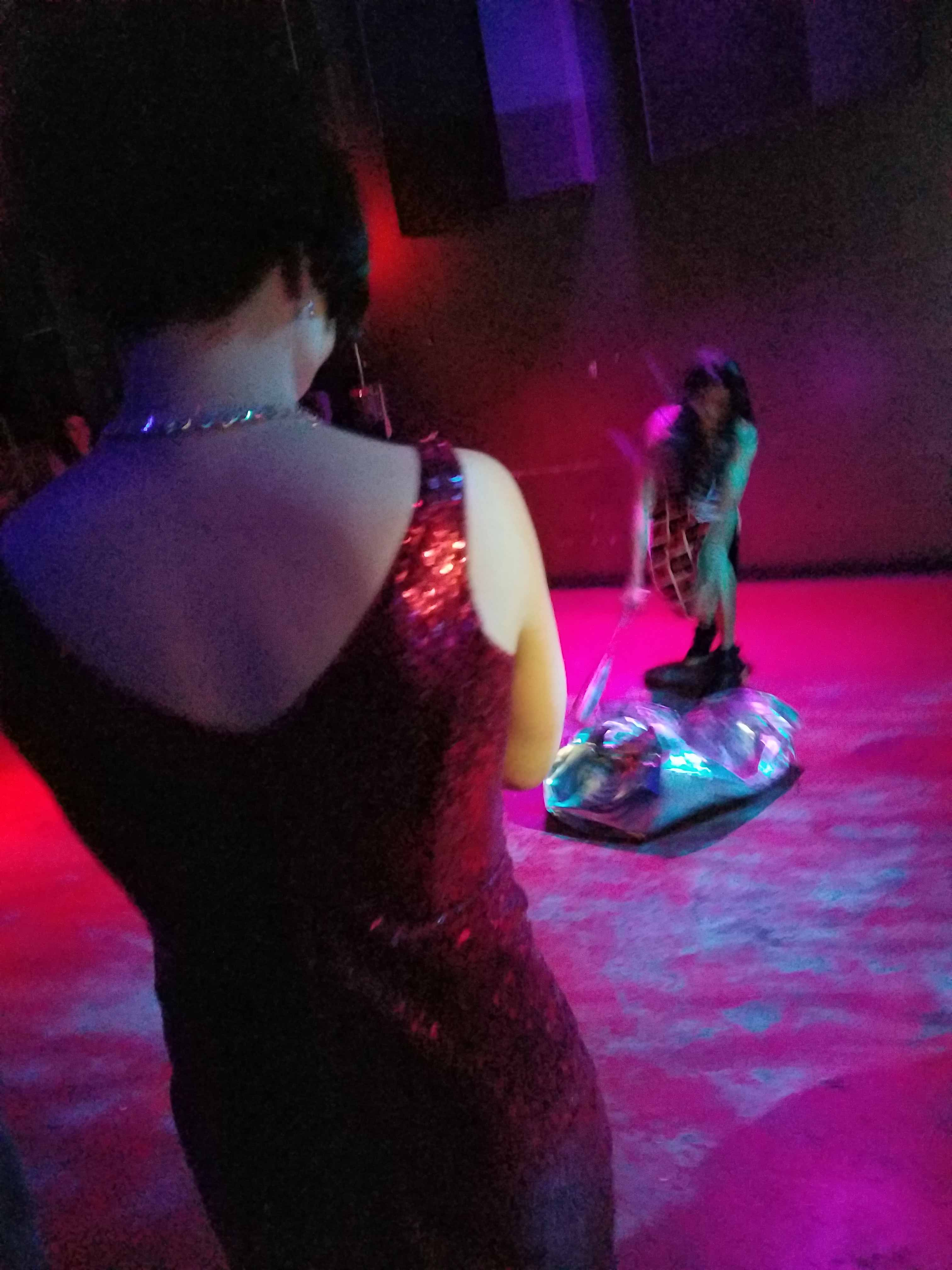 A blurry photo in a dark nightclub of a person smashing a silver trash can with a baseball bat. The photo is taken over the shoulder of a person in a red sequinned dress and short dark hair.