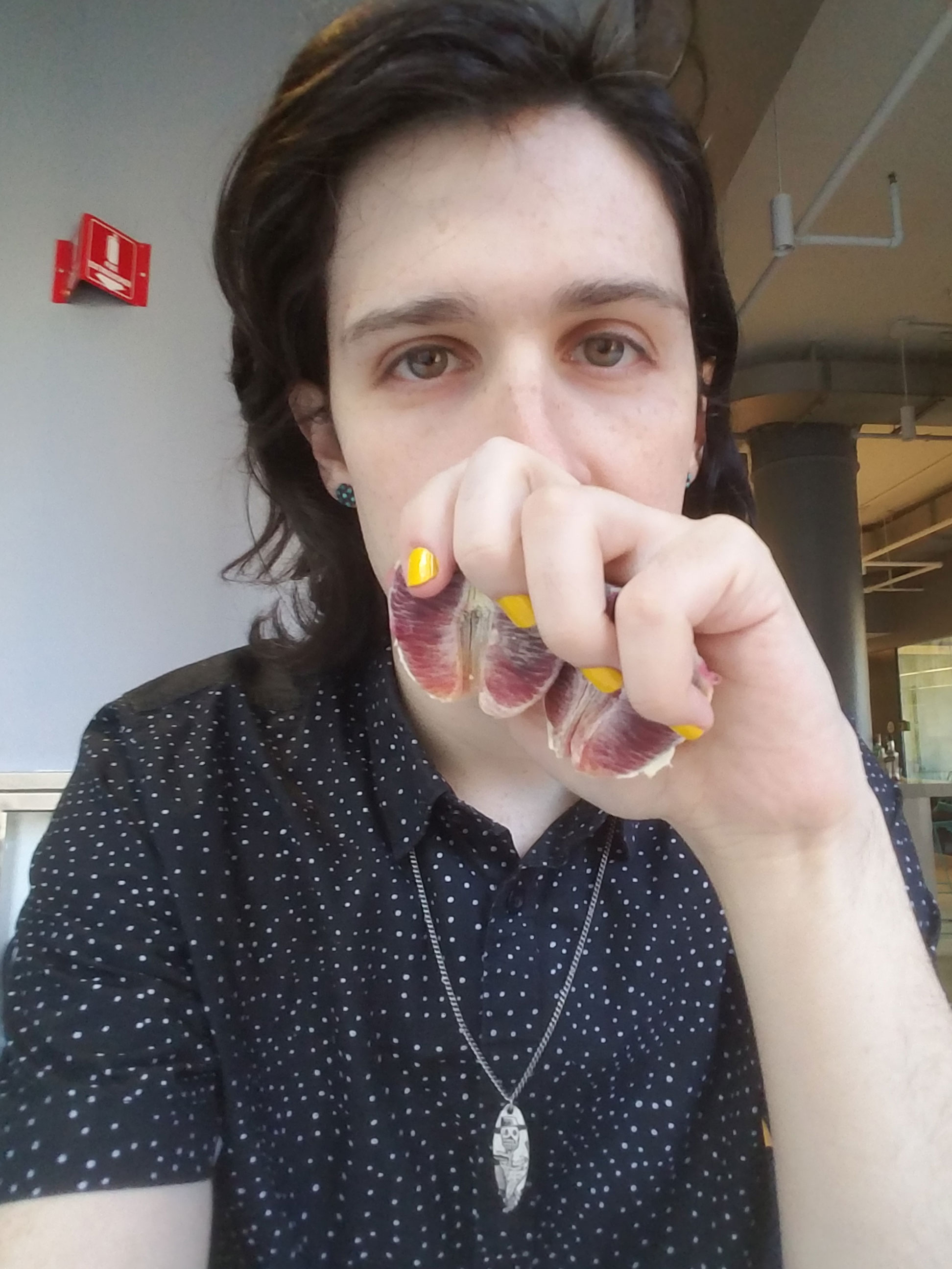 A selfie of a person, wearing a black and white dotted shirt and bright yellow nail polish, and holding two halves of blood orange segments in front of their mouth.