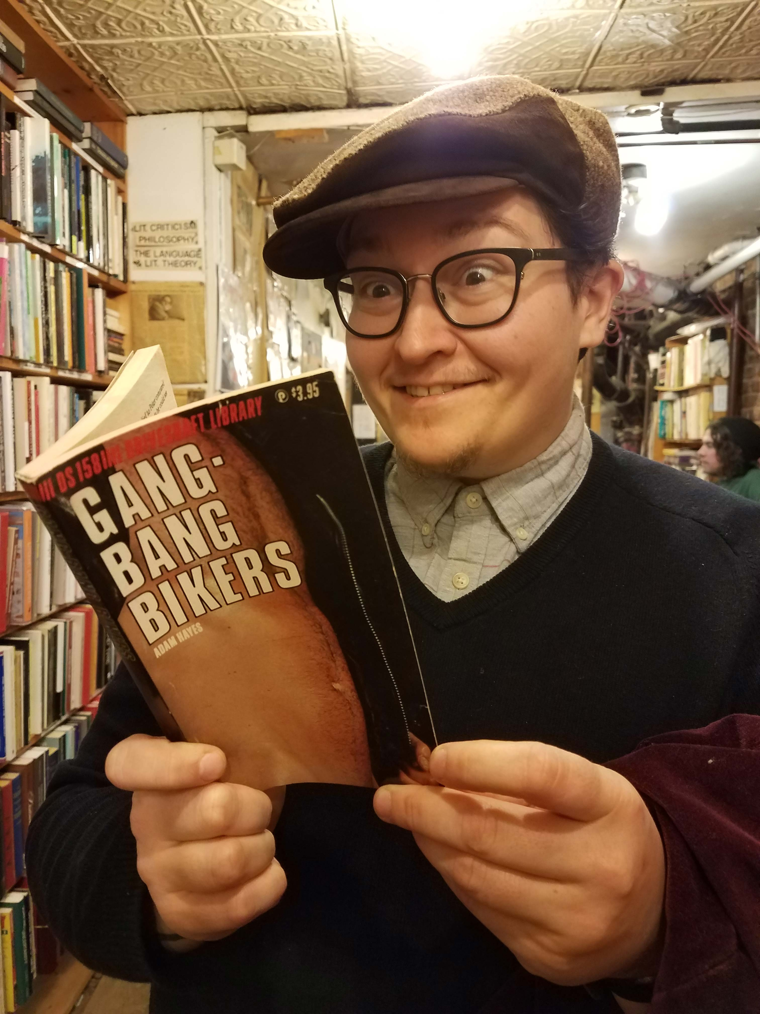 "A person reading a book in a cramped bookstore, wide eyed and grinning. The book's cover reads ""GANG-BANG BIKERS"" and shows a person's bare chest."