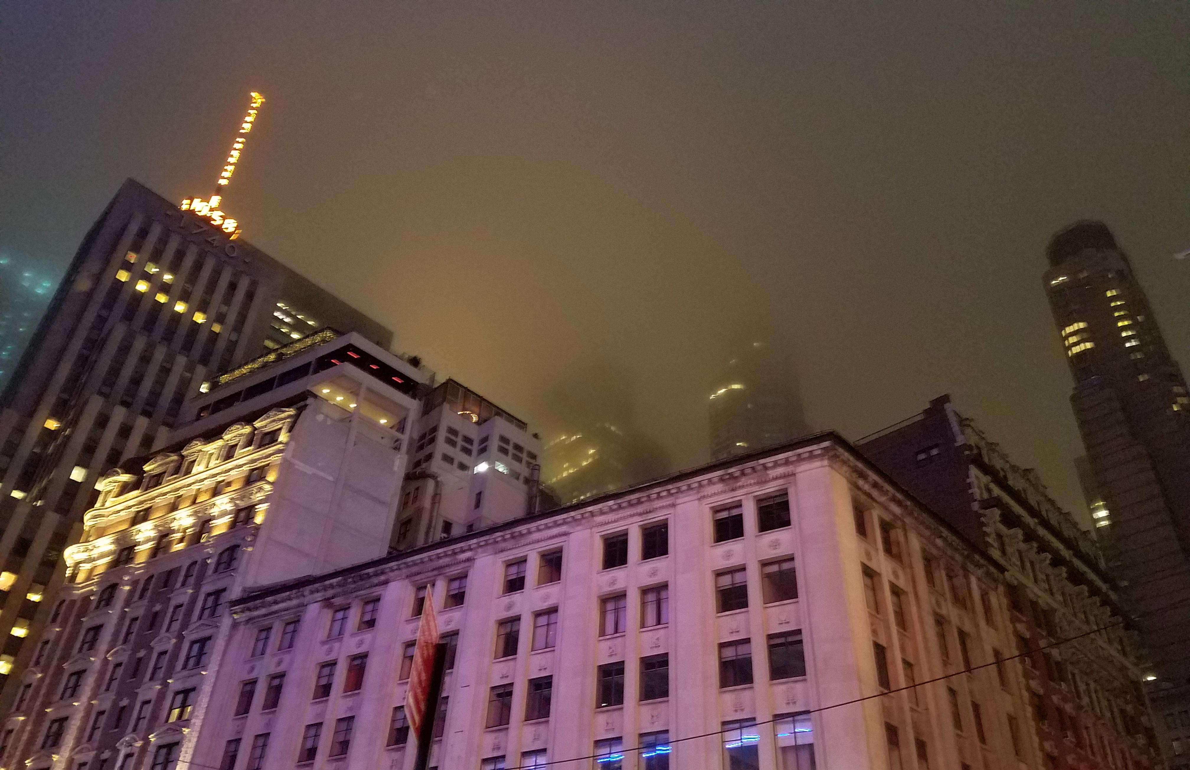 A nighttime picture looking up at a skyline being dissolved by dense fog.