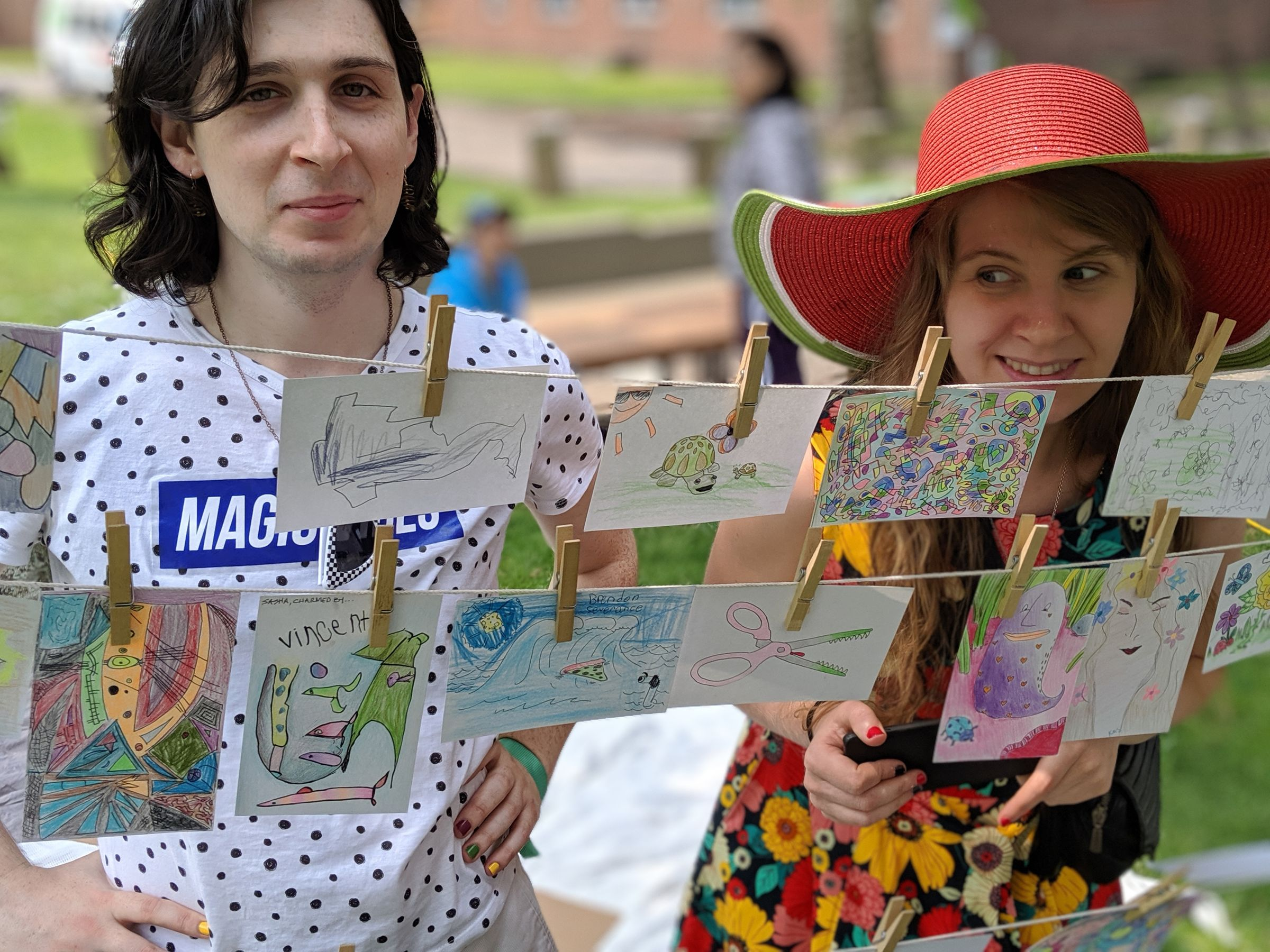 Two people standing behind three clotheslines with colored index cards hanging from it. On the left, one person looks into the camera smiling. Next to them, a person in a colorful dress and a bright sun hat looks at them.