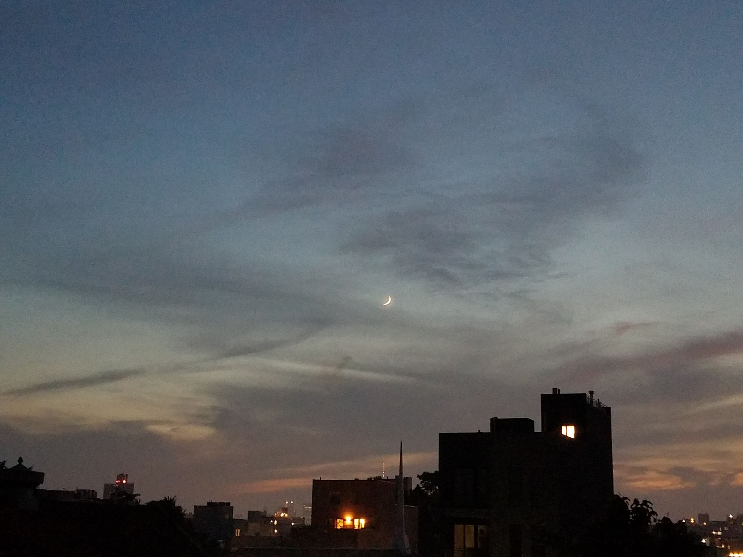 Photograph taken at dusk of a dark skyline under a blue sky, with a hint of sunset on the horizon, covered in patches of wispy clouds. The moon is barely crescent, and is the only visible object in the sky.