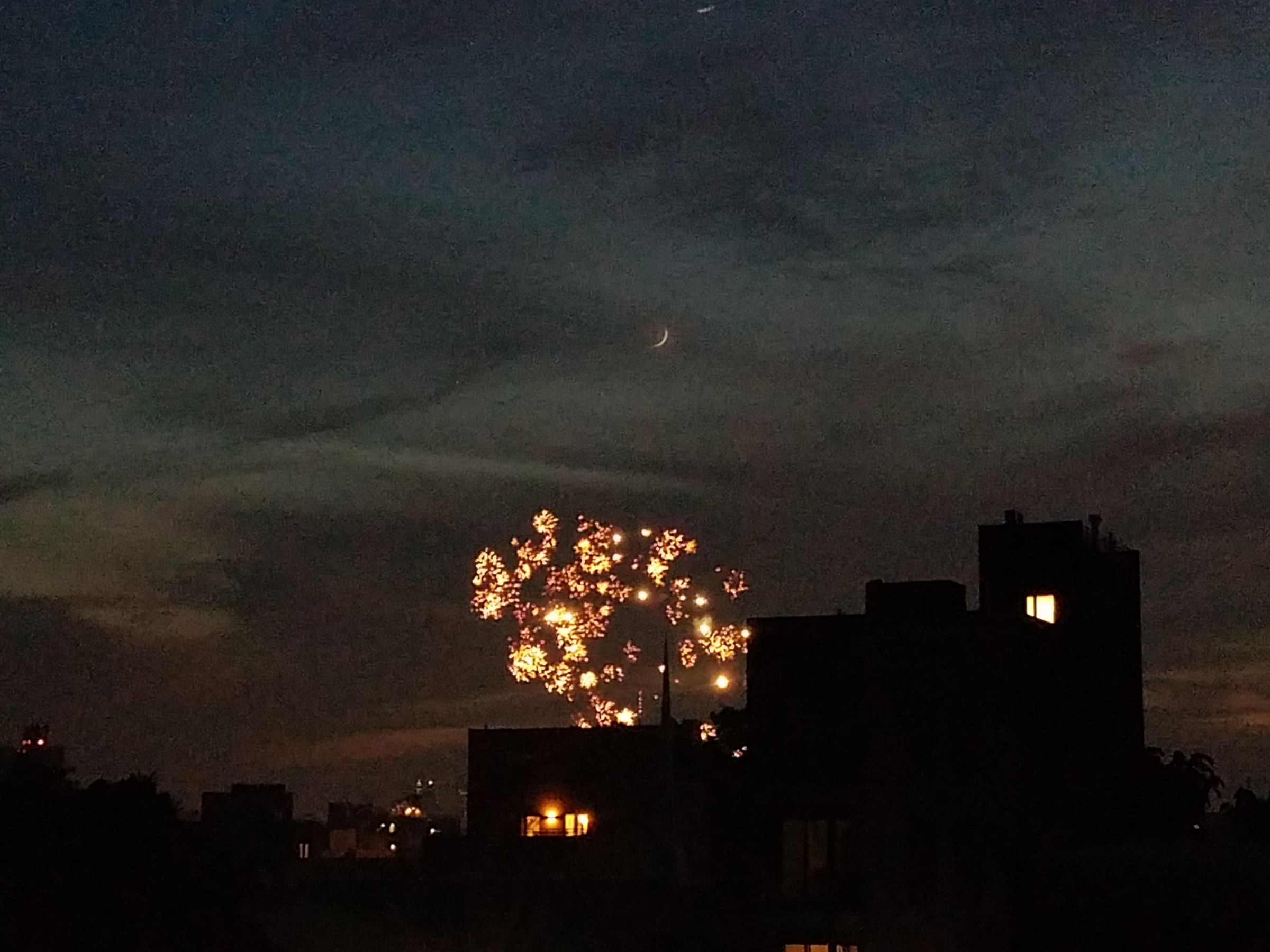 Photograph taken at night of a dark skyline barely visible against a cloudly night sky. The moon is barely crescent, and below it yellow fireworks explode.