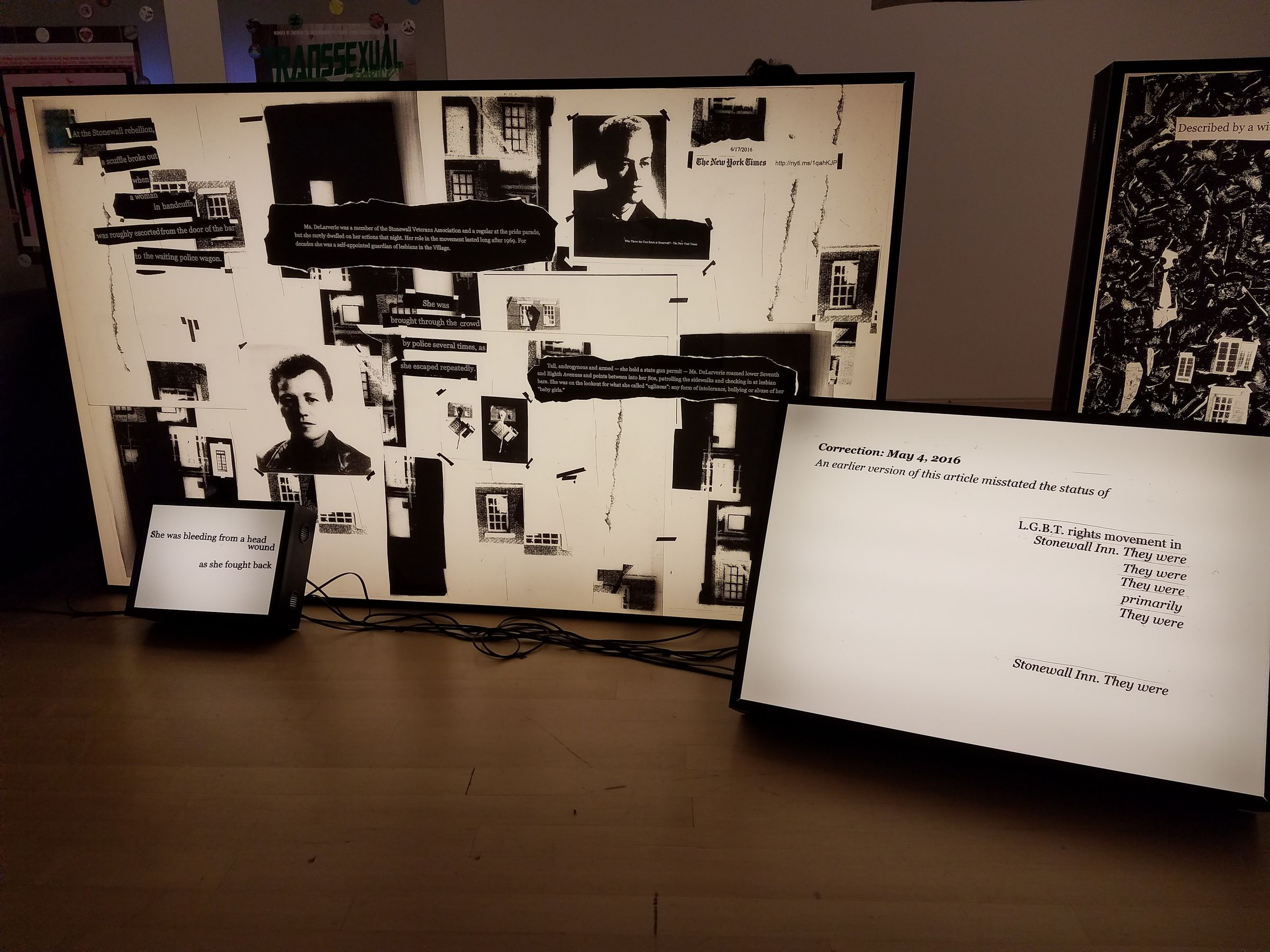 "An indoor art installation consisting of multiple backlit panels showcasing arrangements of black-and-white newspaper clippings. Three panels are completely visible in the picture. The smallest is white with black typewriter text: ""She was bleeding from a head / wound / as she fought back"". Another reads: ""Correction: May 4, 2016 / An earlier version of this article misstated the status of / L.G.B.T. rights movement in / Stonewall Inn. They were / They were / They were / primarily / They were / Stonewall Inn. They were"" The largest panel, which the others lean against, is a collage of headshots, pictures of windows and doors, and newspaper clippings."