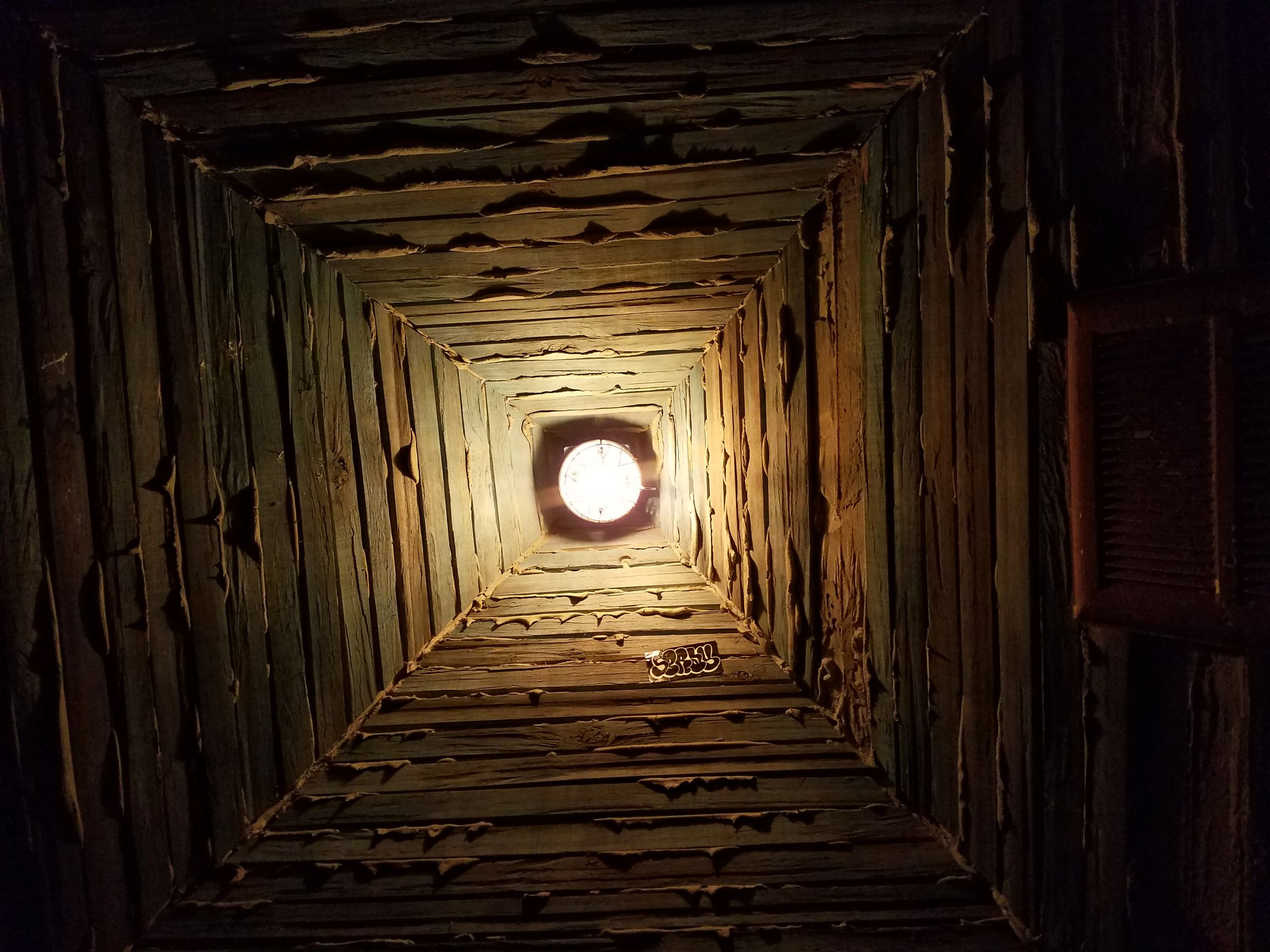 A photograph taken facing upward toward a pyramidal ceiling made from wooden slats and dripping with dried caulk where they join. It is illuminated by a single yellow lightbulb that casts some stark shadows onto the textured ceiling.