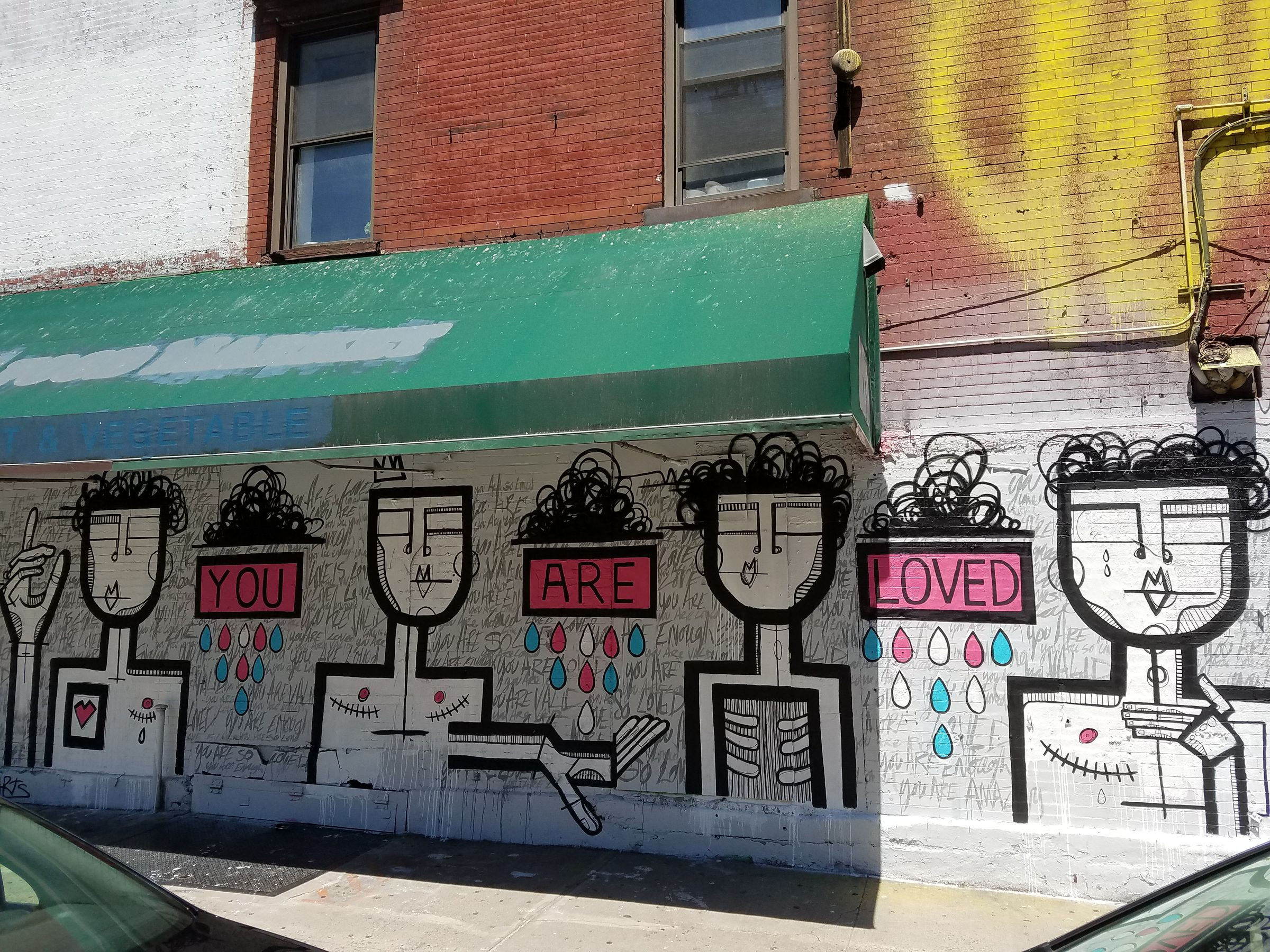 "An exterior wall mural under an awning. There are four busts of people, most with outstretched arms and stitches from top surgery. Some have cutouts exposing their stylized innards. The phrase ""You Are Loved"" is spread out between the figures, and each word drips pink, blue, and white tears."