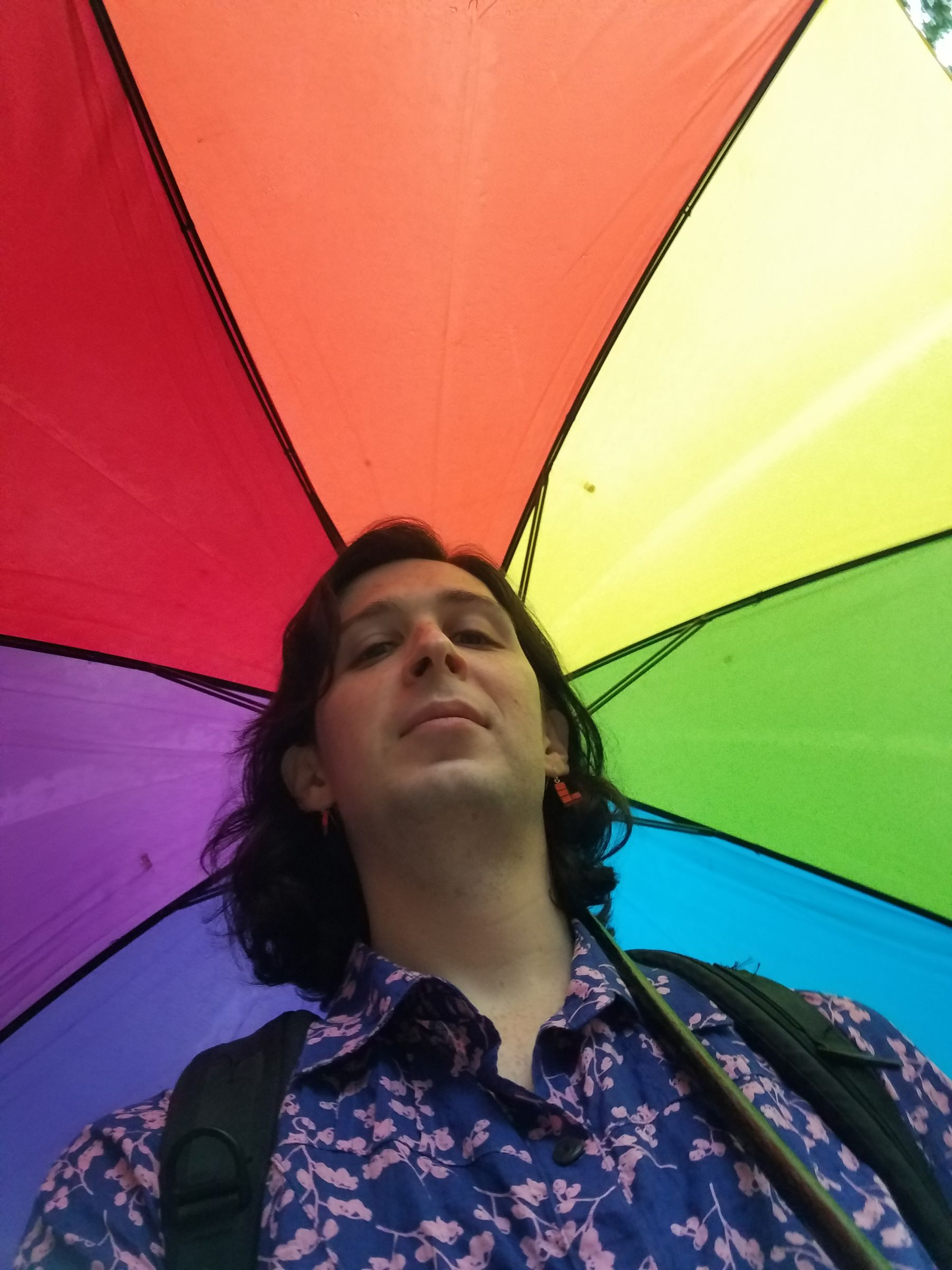 A person under an rainbow colored umbrella. The photo is taken from below and looking up, so their umbrella is the background framing their face.