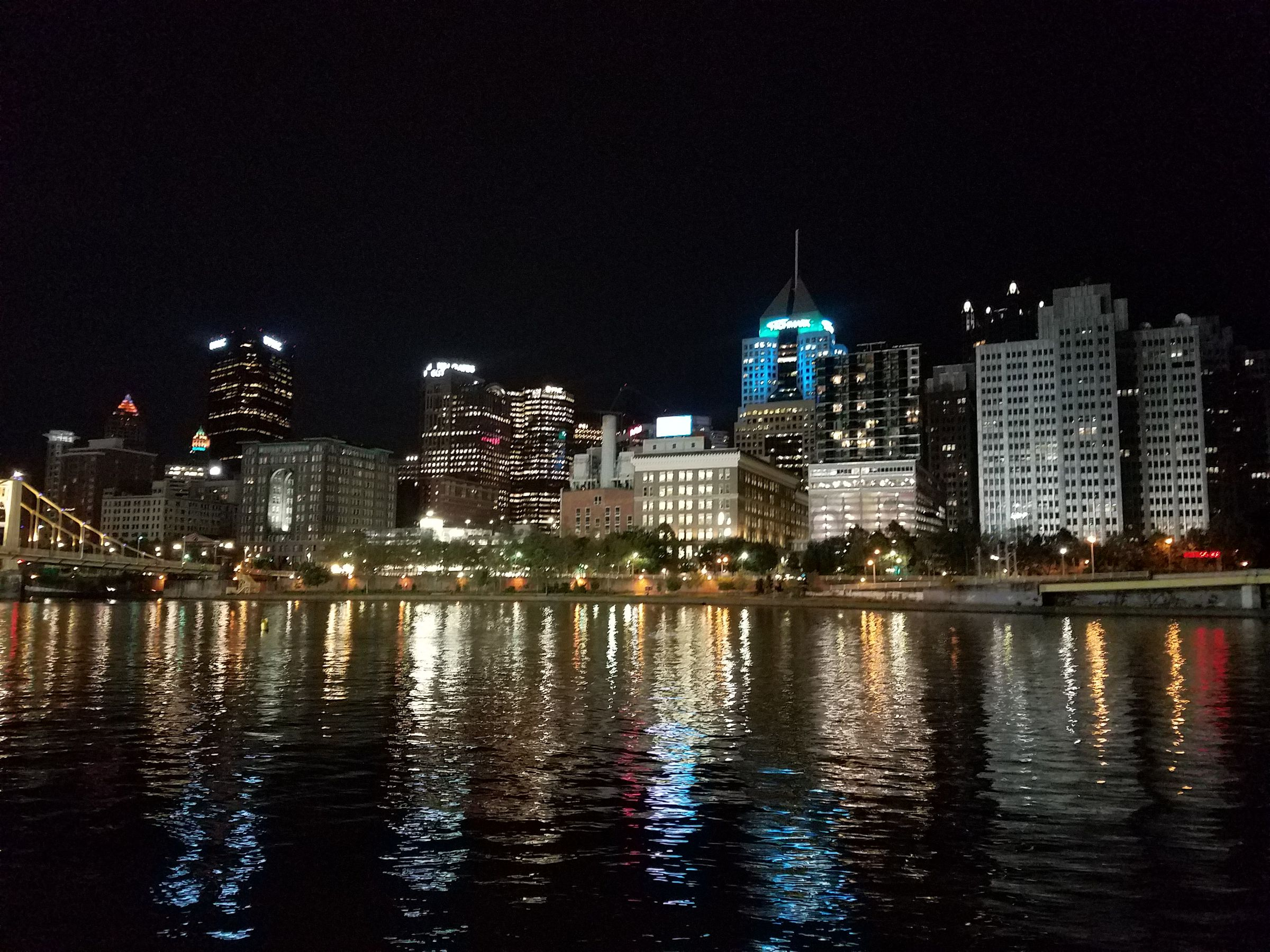 A nighttime view of downtown Pittsburgh from the north shore, across the Allegheny River. The water reflects the light from windows and street lamps.
