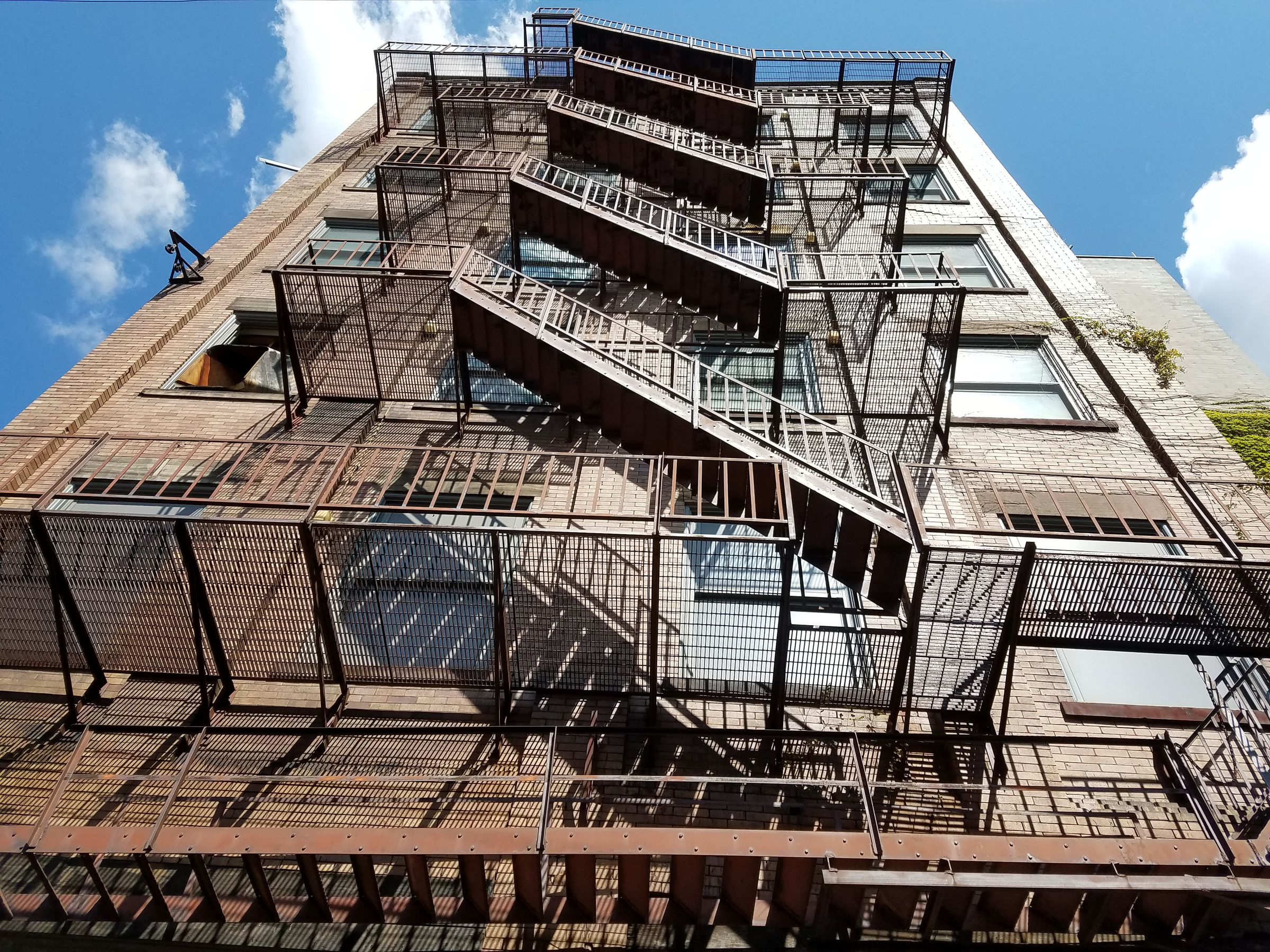 Looking up from street level at the exterior of a 6-story red brick building. The face of the building reflects a bright morning sun, and a fire escape casts sharp shadows on it. The sky clear blue, aside from a couple clouds.