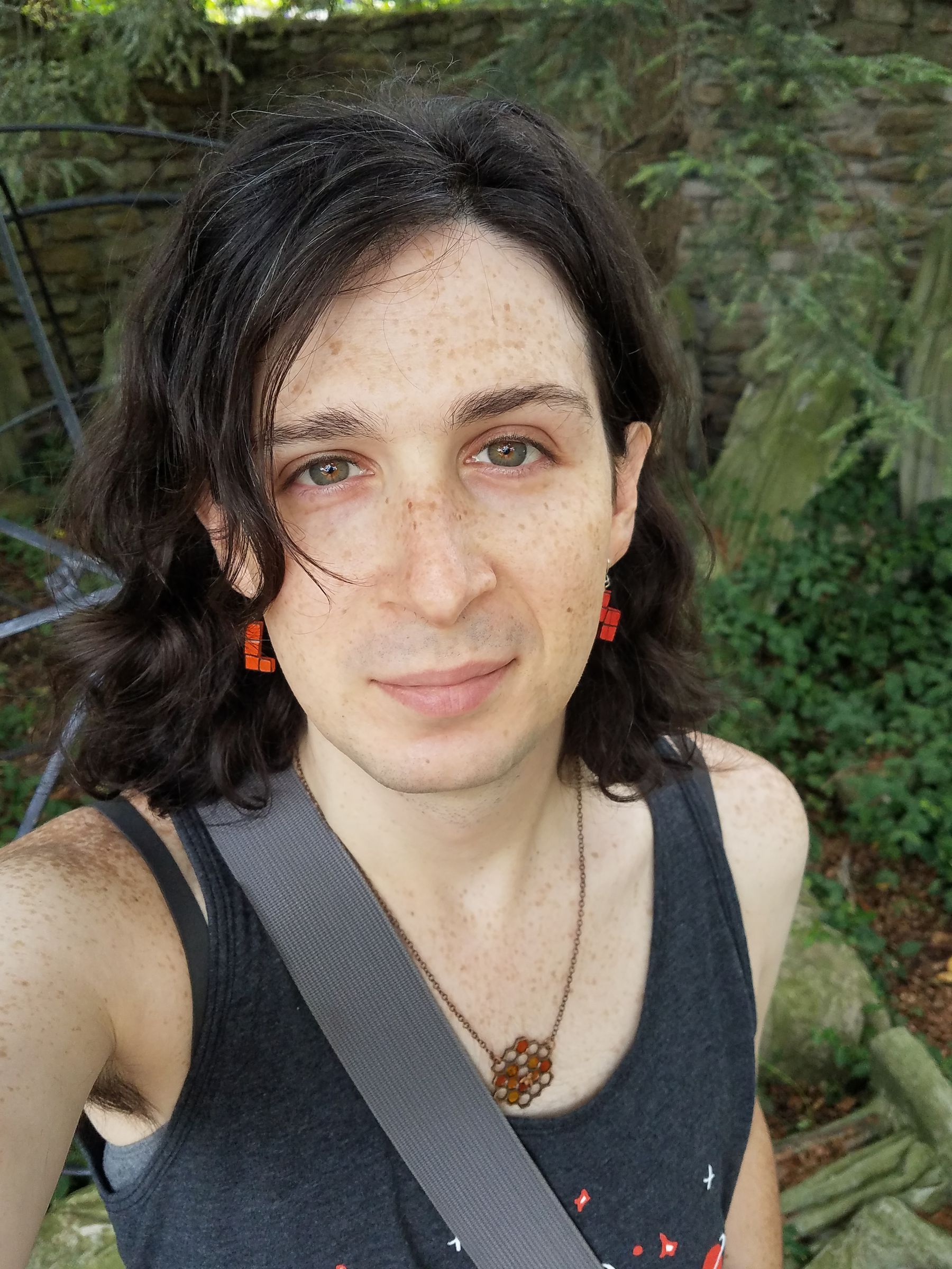 A selfie of me from my chest up, wearing a tank top and orange tetronimo earrings, taken in a walled-in corner outside the Mattress Factory Museum. Behind me are toppled stone statues covered by creeping plantlife. There is a metal wireframe ball about the diameter of an adult barely visible behind me.