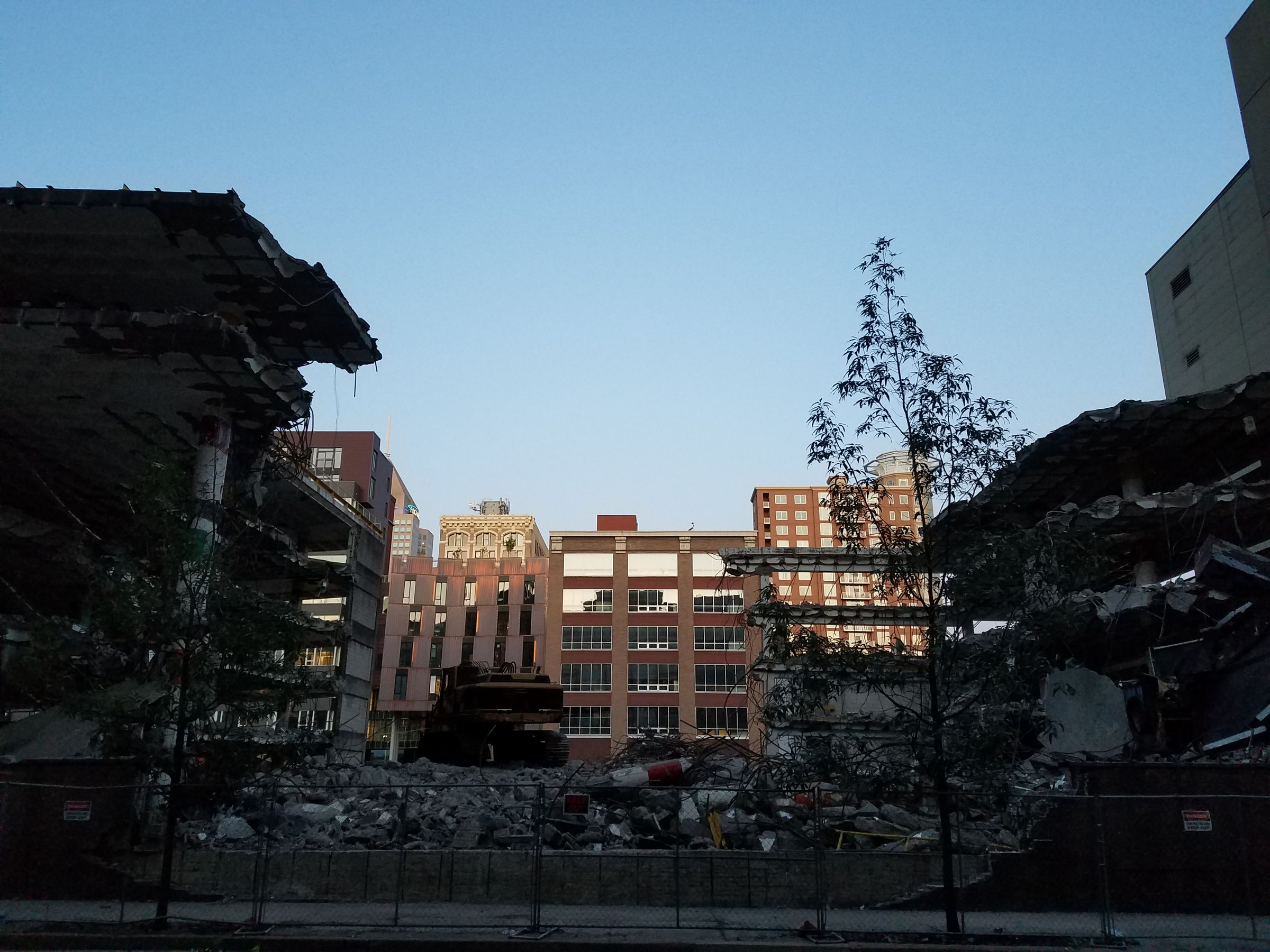 A partly demolished parking garage. It looks like there is literally a bite taken out of it. The multi-level garage is intact on the left and right sides of the photo, but the space between is a pile of rubble. You can see the next city block behind it.