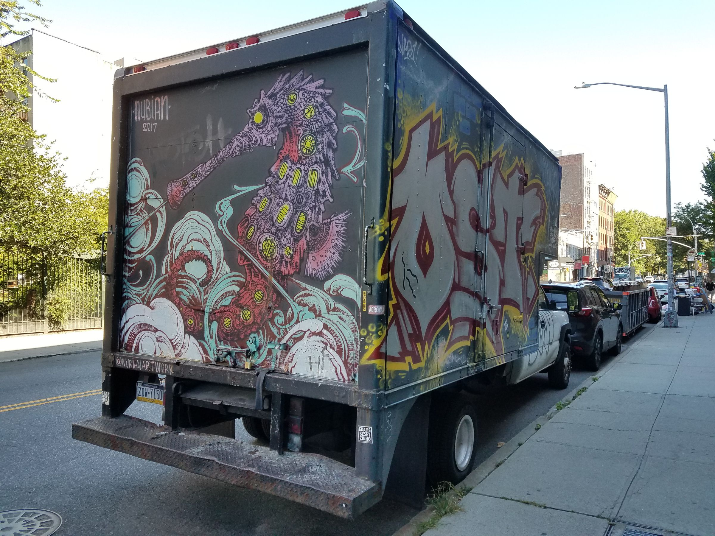 A box truck parked on the side of a city street, covered in art. The rear side features a red and purple mechanical seahorse with yellow grated windows on its body. Its lower body is enveloped in swirls of light blue smoke. The bed of the truck is tagged @NubianArtwork.