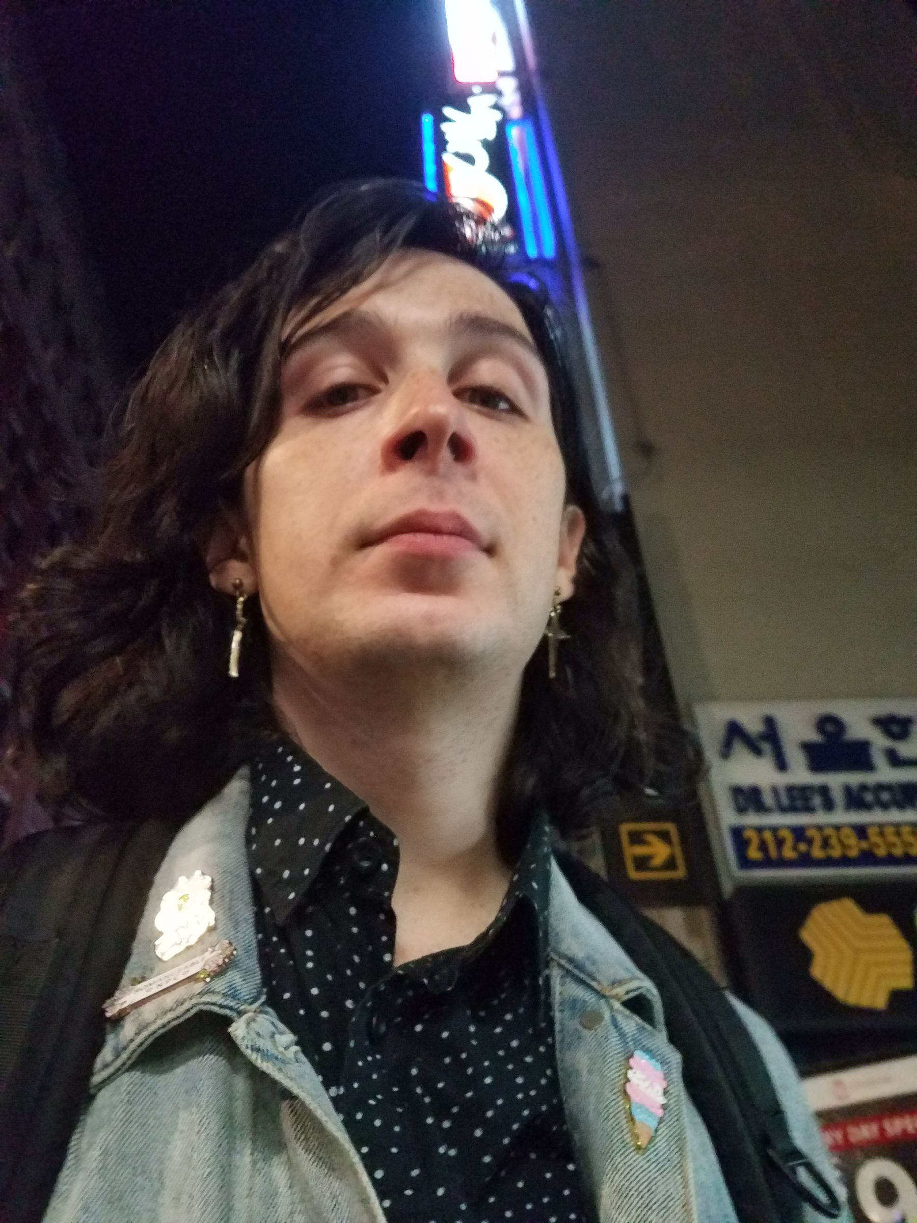 Upward looking selfie at night, taken on a city street with neon signage in the background. I'm wearing a denim jacket with pins on each lapel, over a white-on-black dotted button-down shirt.