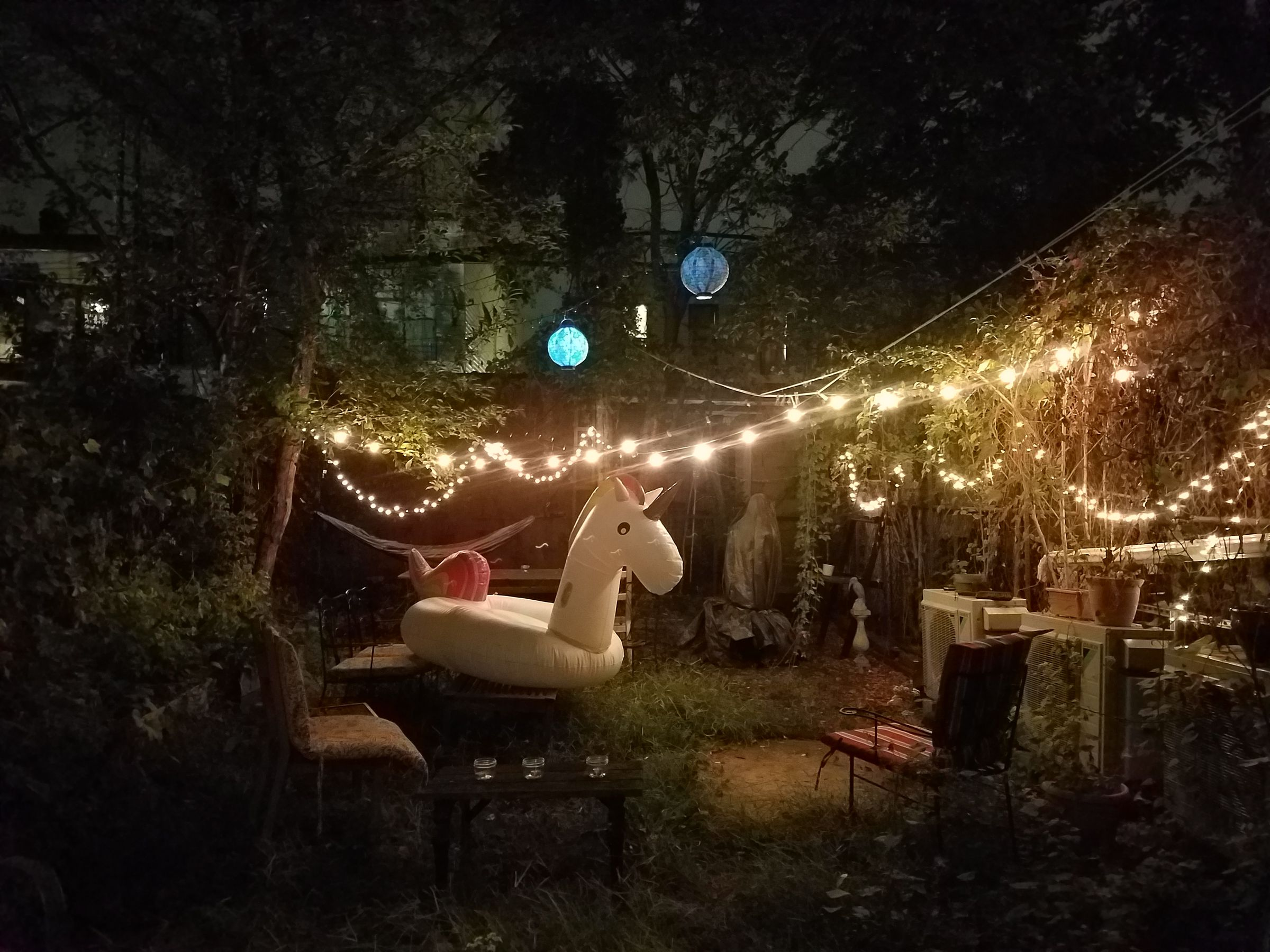 A grassy, urban back yard at night, illuminated by a couple of hanging crepe lanterns and several strings of lights. A white inflatable pool unicorn rests on a table and bench.