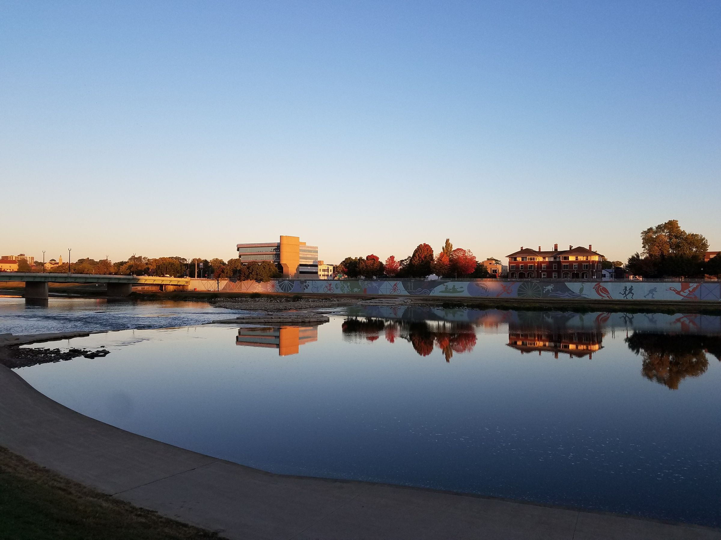 A photo taken in the morning across a quiet river. The far embankment is covered in a mural depicting birds, fish, and outdoor activities like running, cycling, and ice skating. The sky is clear, and the sun is just starting to strike the opposite bank.