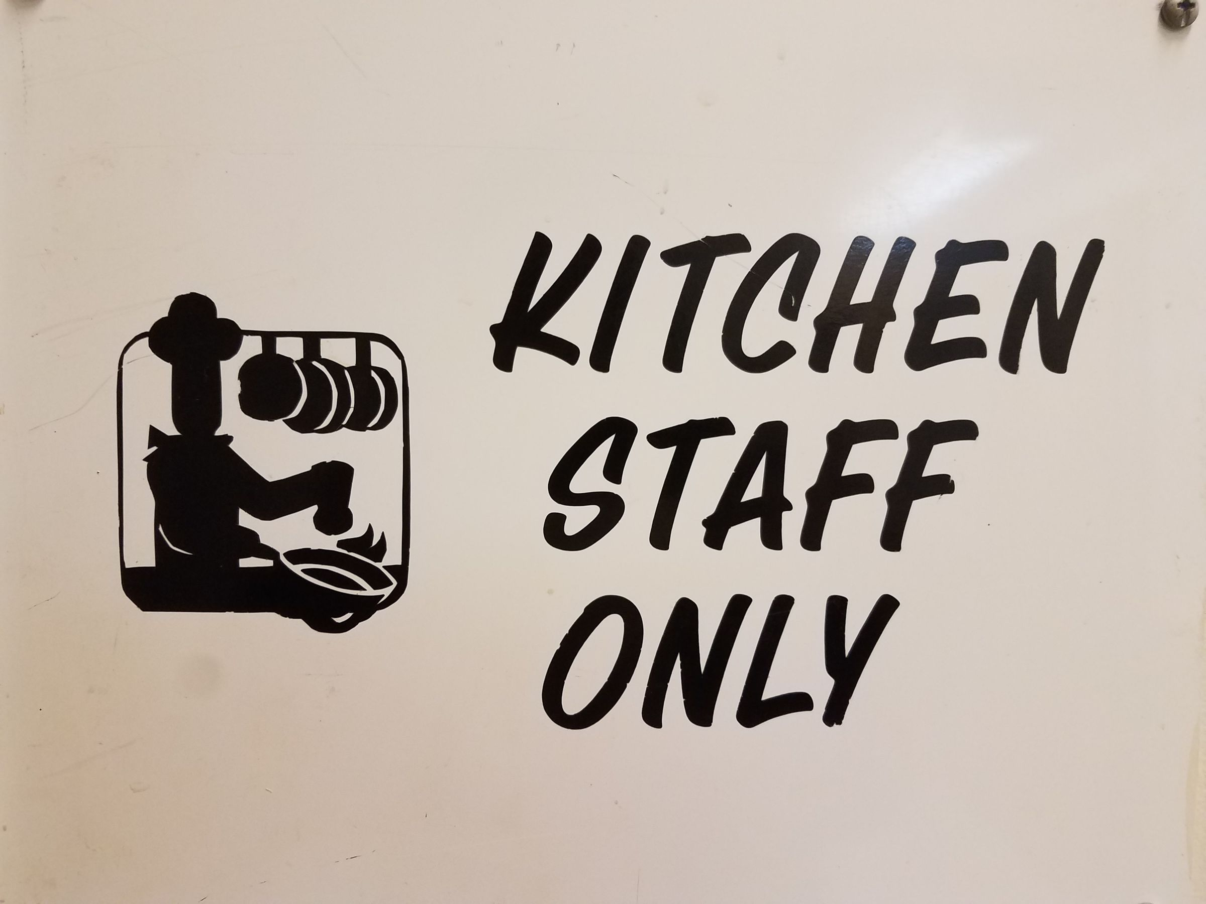 "A white sign with black lettering that says ""Kitchen Staff Only"". To the left is a graphic of a cook holding a pan over a flaming stove top, sprinkling spices into it. Its silhouette gives the person the appearance that their head is a single round bulb."