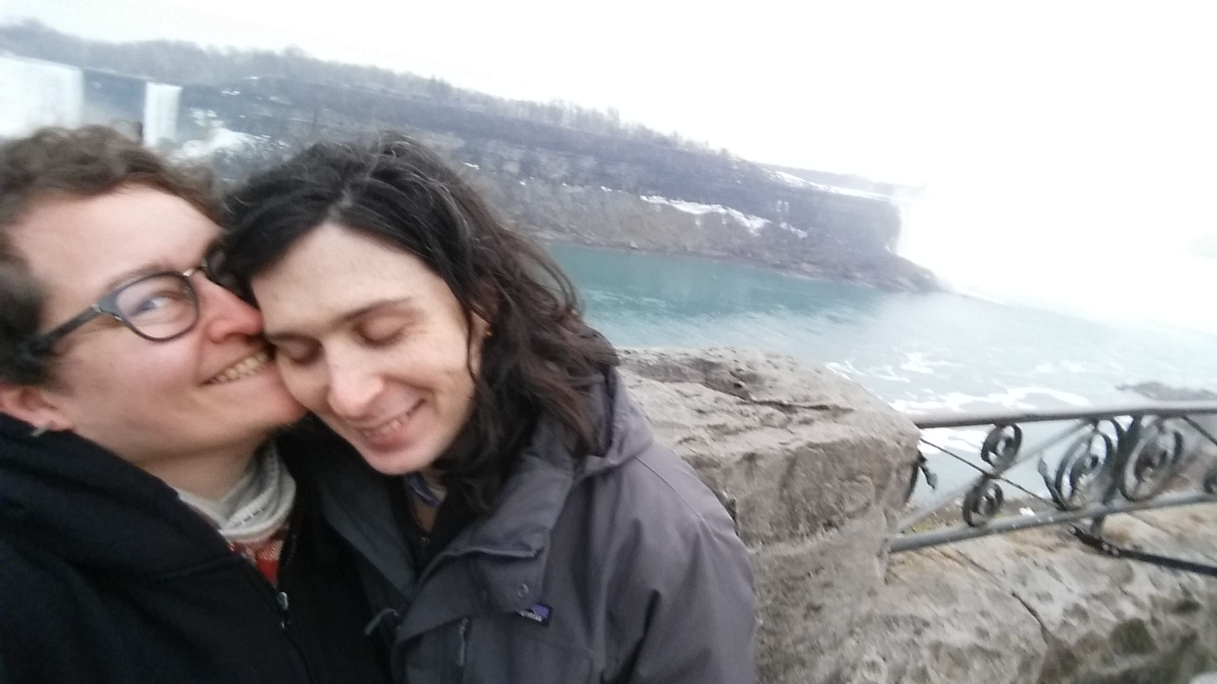 A selfie of two people embracing near the edge of Niagara falls on the Canadian side. One person is smiling into the camera, and the other person is smiling with their face turned down, eyes closed.