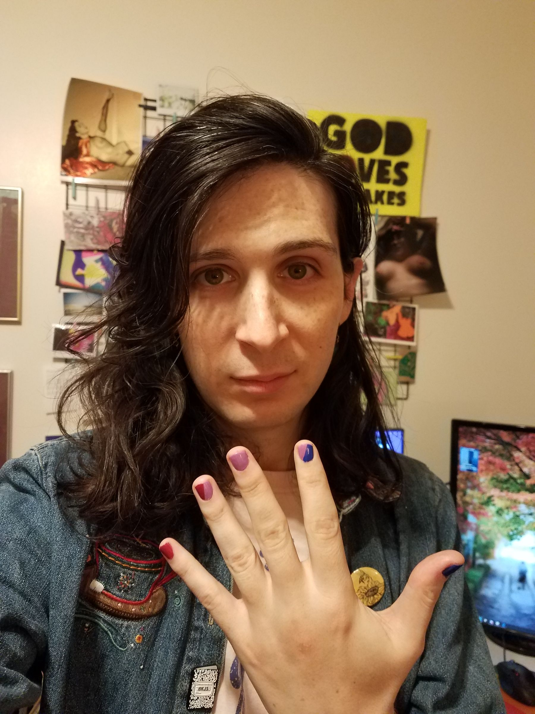 Indoor selfie of a white queer with shoulder length brown hair, holding their hand up to the camera to show off their nail polish in bi pride colors. In the background there's a computer monitor on a desk, and an art collage on the wall.
