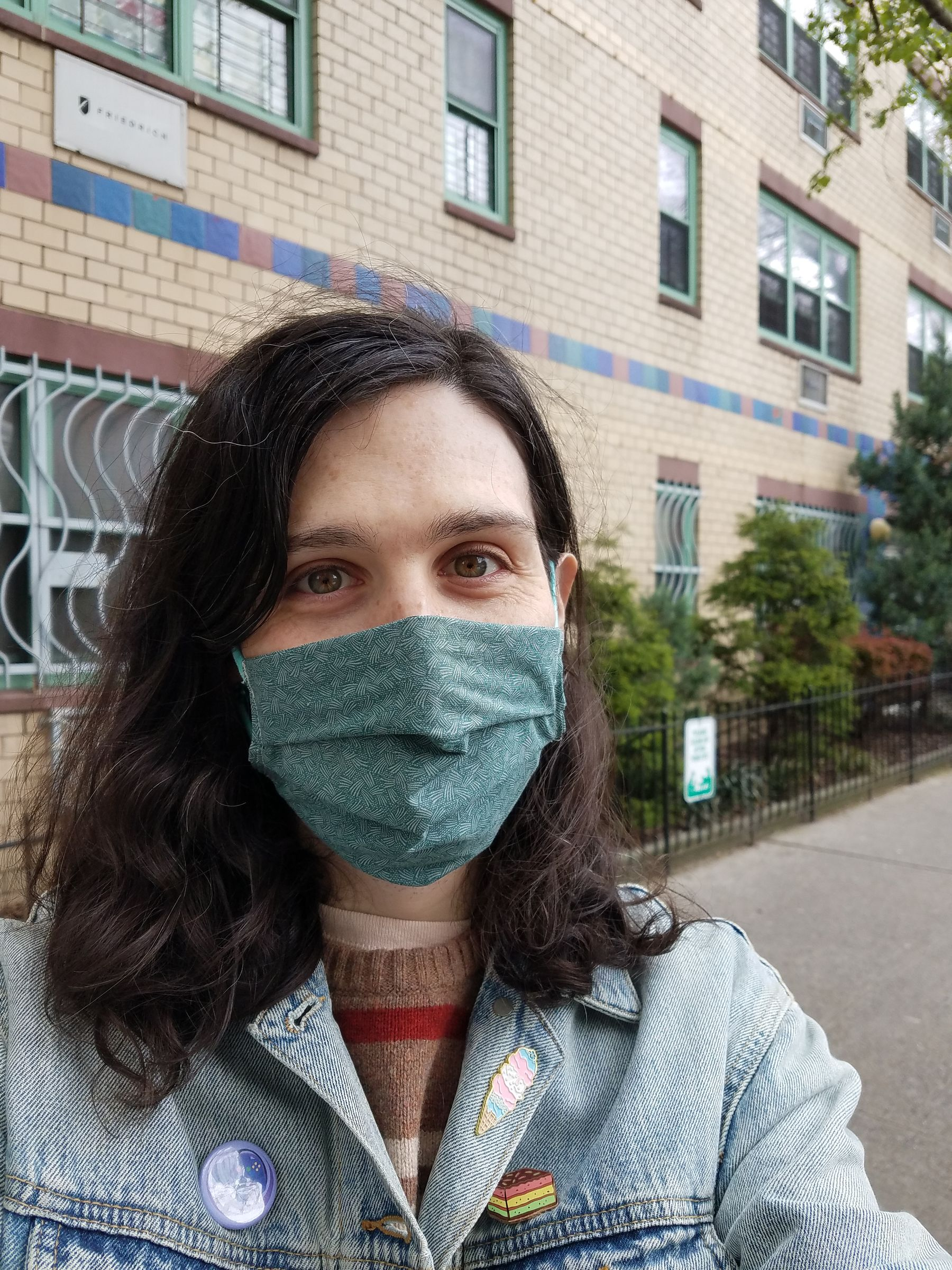 Sidewalk selfie of me, with shoulder length brown hair, wearing a denim jacket and a teal cotton mask.